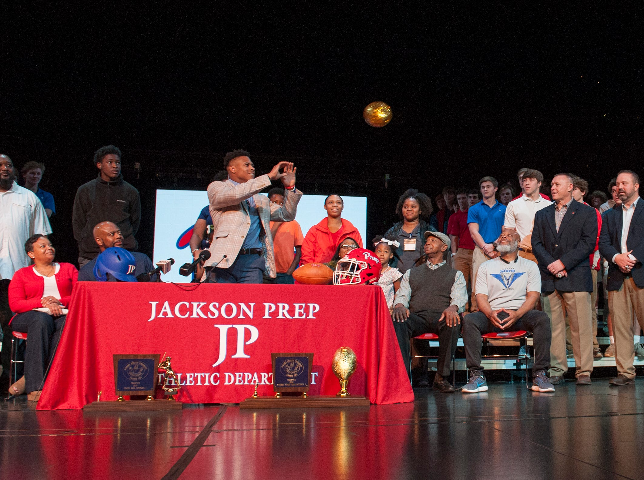 Jackson Prep's Jerrion Ealy receives a gold-sequence-coved football passed to him by Prep's head coach Rickey Ealy during Signing Day at the school Friday, Feb. 6, 2019. Inside the ball is a cap indicating his choice of university. Shortly thereafter, he put on an Ole Miss cap, topping it off with the Landshark gesture.