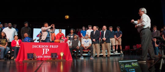 Jackson Prep's Jerrion Ealy receives a gold-sequin-coved football passed to him by Prep's head coach Rickey Ealy during Signing Day at the school Friday, Feb. 6, 2019. Inside the ball is a cap indicating his choice of university. Shortly thereafter, he put on an Ole Miss cap, topping it off with the Landshark gesture.