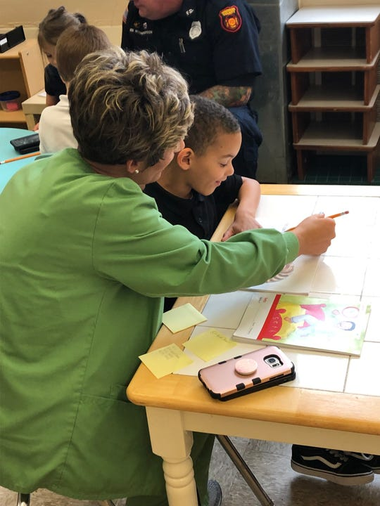 Sebastian Wilbourn reads with his mom, Bridgett Andrews, during Community Montessori's 100th day of school celebration. Each kindergarten class was challenged to read 100 books in 30 minutes. The four classes, in all, read 1,013.