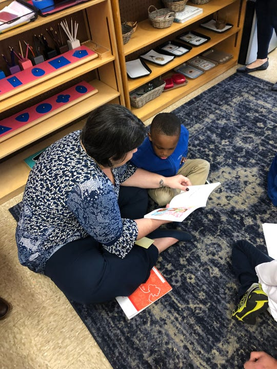Shawn Reeves reads to Rachel Scott, the leader of professional development for JMCSS.