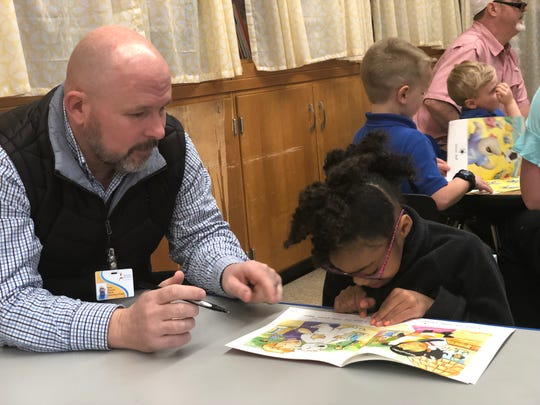 Kaylee Green reads to JMCSS board member Kevin Alexander at Community Montessori's 100th day of school celebration.