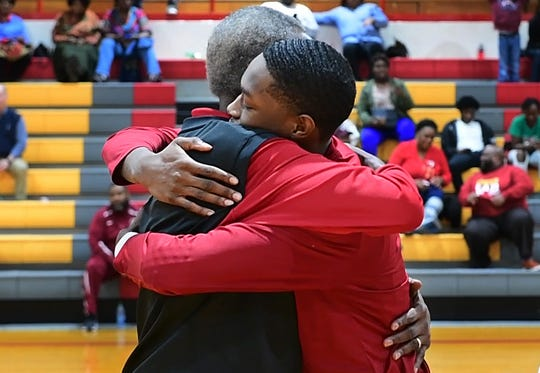 Humboldt coach Ron Abernathy hugs his son and senior basketball player, RJ, during Senior Night festivities before the start of their game against Middleton on Tuesday.