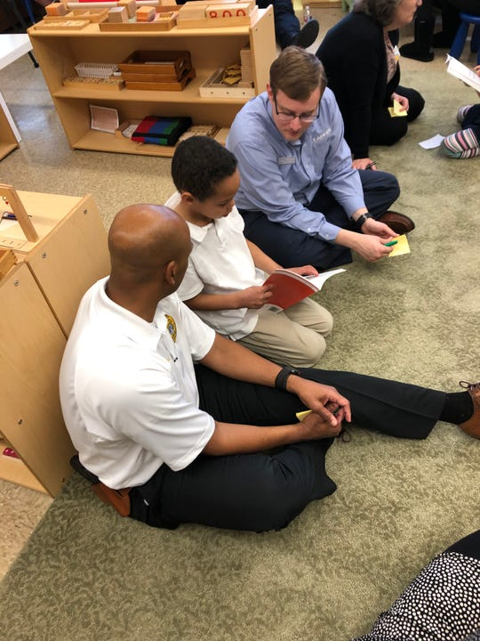 Martese Coleman reads to his two buddies, JPD Deputy Chief Tyreece Miller, left, and Shea Brown of Leaders Credit Union.