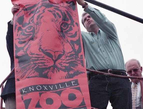 Knoxville Mayor Victor Ashe, behind banner, and Knoxville Zoo director Patrick Roddy place the first banner on a light pole in downtown Knoxville in May 1998. The banners celebrate the 50th anniversary of the zoo.