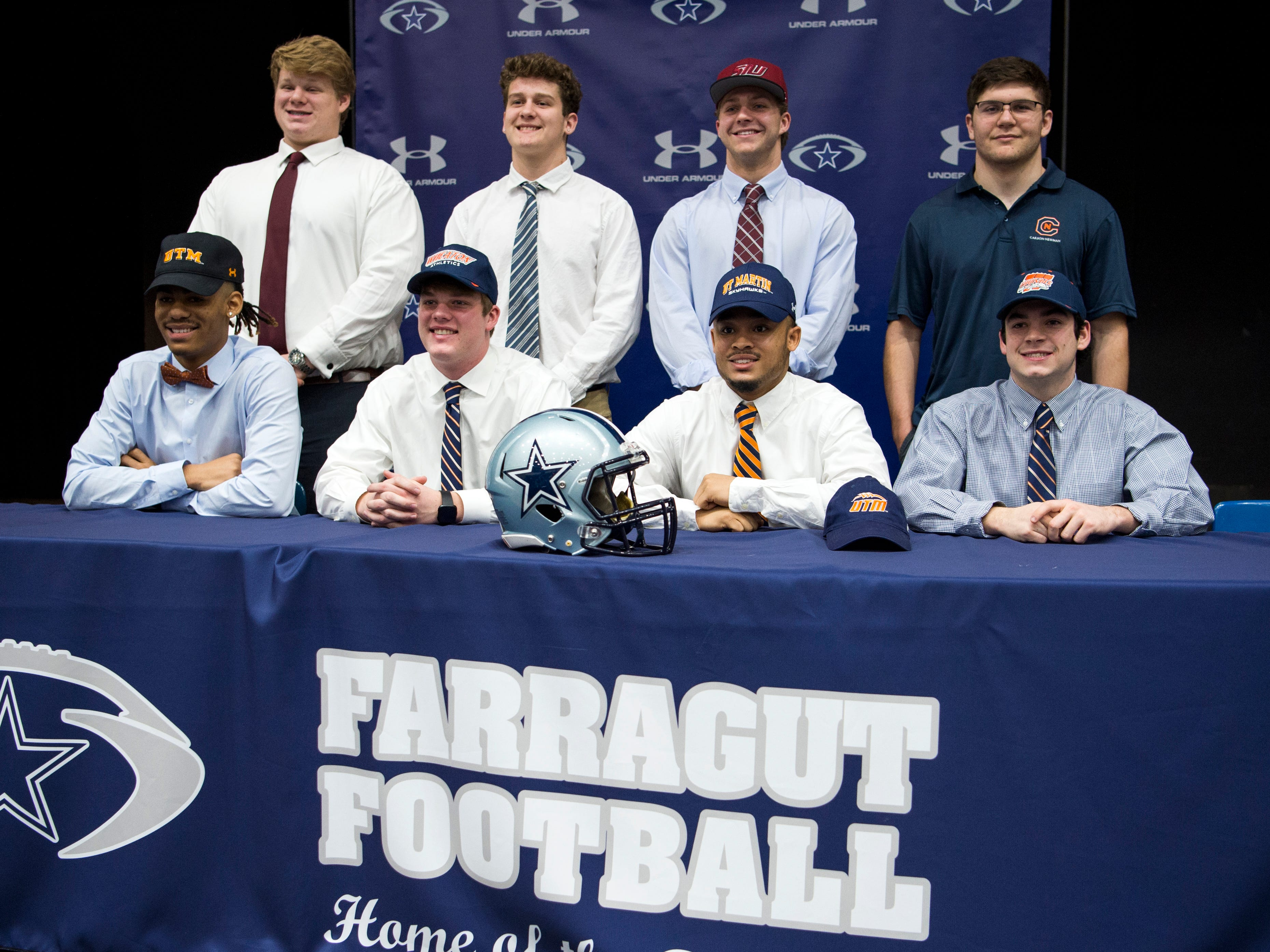 Farragut football players sport their new school colors at the FHS auditorium on National Signing Day, Feb. 6, 2019. Pictured are (front) Jaden Gibbs (UT Martin), Caleb Kuhn (Wheaton College), Isiah Gibbs (UT Martin), Kyle Carter (Wheaton College); (back) Ethan Gossage (Campbellsville), Jake Parsons (Carson-Newman), Tanner Corum (Southern Illinois) and Joey Dietz (Carson-Newman).