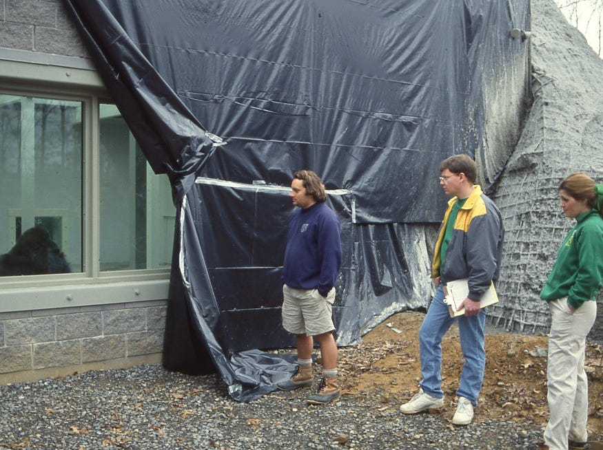 Primate keeper Gene Peacock, left, and zoo volunteers David Hamilton and Tina McConnell look through the windows at Scotty, a 343-pound gorilla that will be part of the new gorilla and chimpanzee indoor exhibit and courtyard area at the Knoxville Zoo in March 1993.