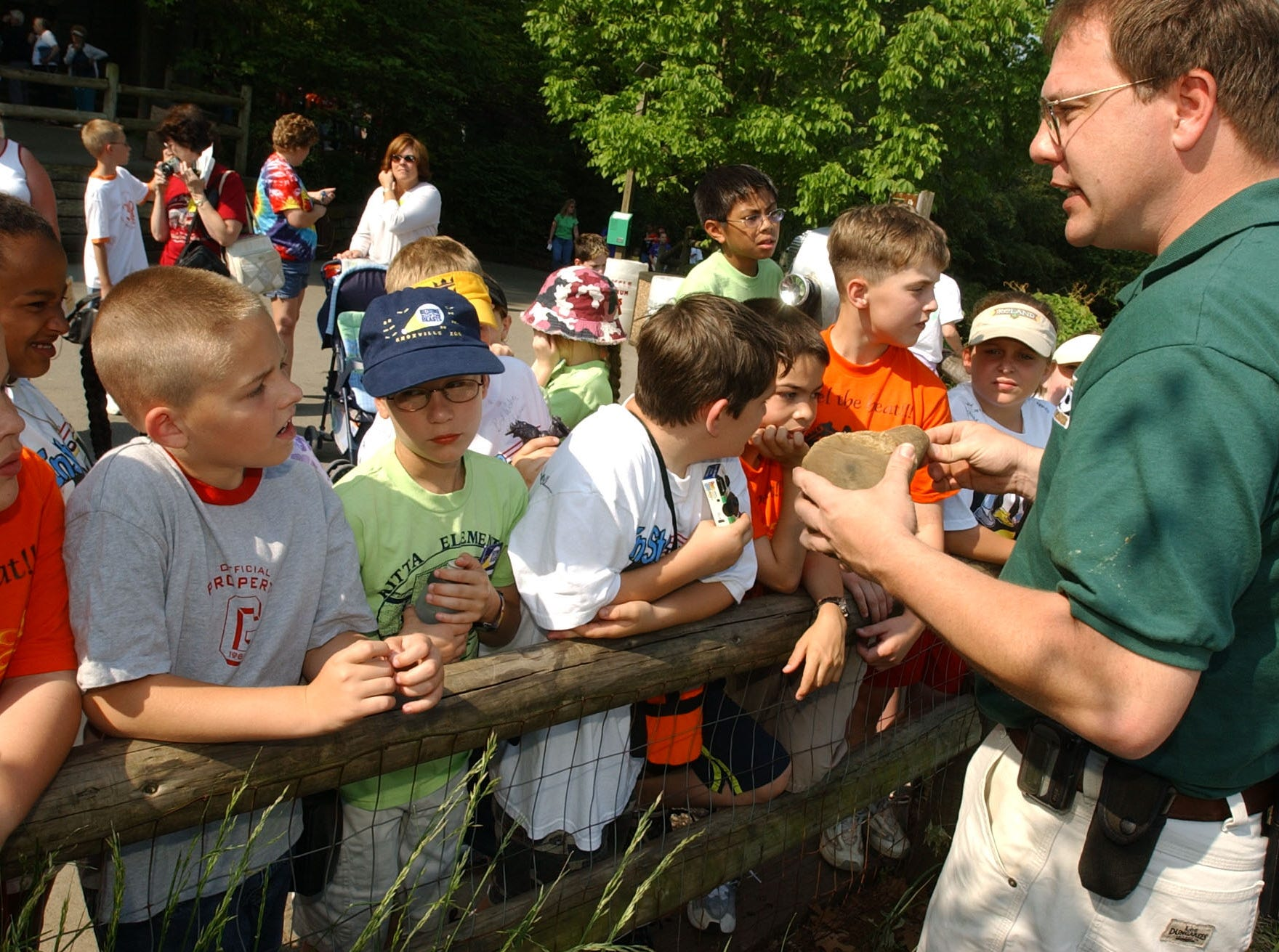 Austin Love, left, and his classmates from Ritta Elementary School listen to curator Terry Cannon, right, explain about Rinos at the Knoxville Zoo.  Students at Ritta raised $1,200 through an inschool reading project to adopt 17 animals at the zoo. The rhino was adopted because Love's father served in the Persian Gulf as a Navy diver in a unit nicknamed Rhino.