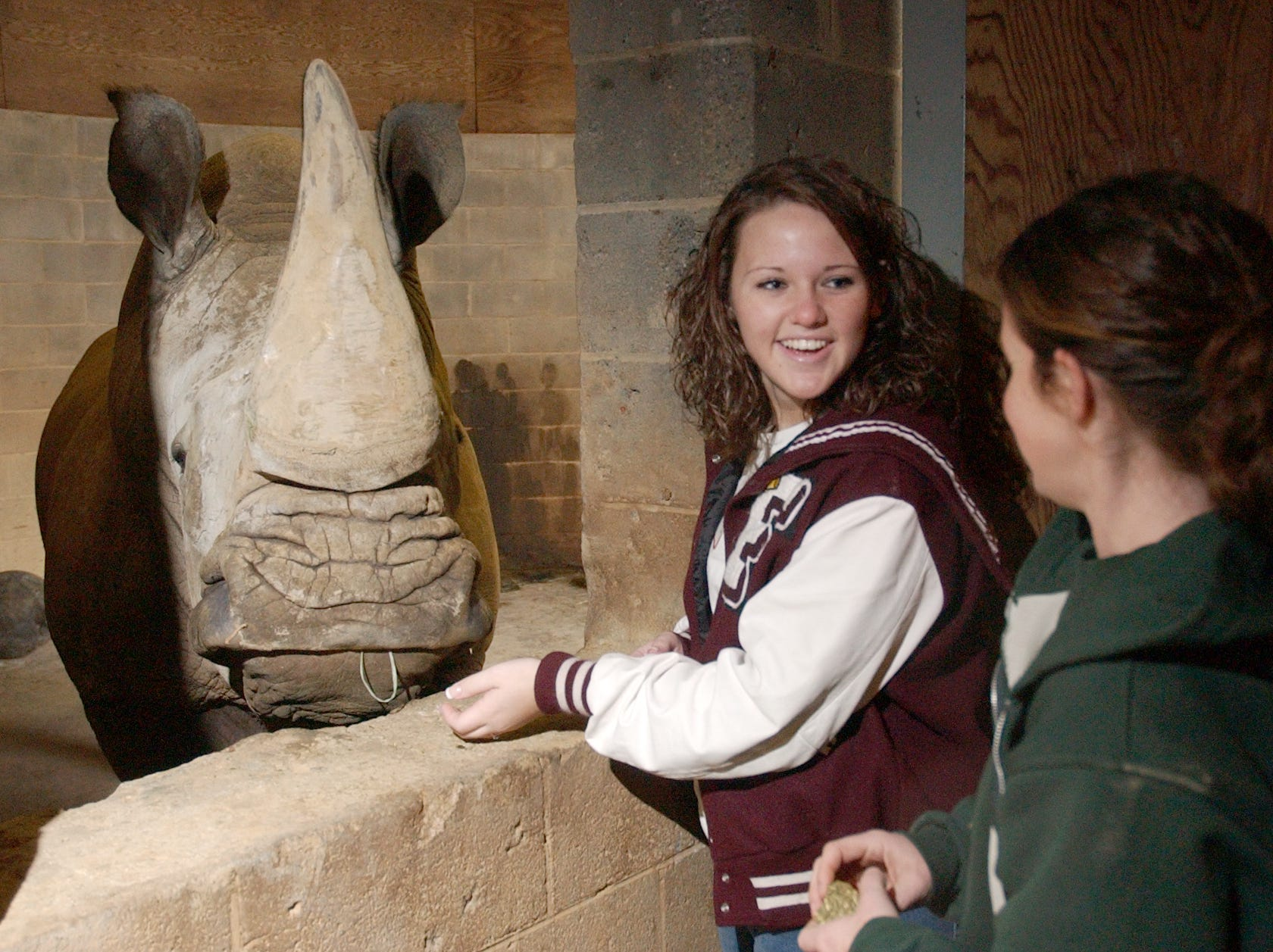 Lyndsey Harris, 16, a junior at Fulton High School, left, hand feeds alfalfa cubes to Mondo, a 5,000 pound Southern white rhino at the Knoxville Zoo as lead rhino keeper Amy Flew looks on Wednesday. Harris was job shadowing Flew. 2005.