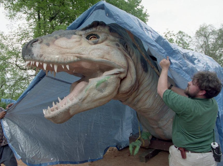 A life-sized Tyrannosaurus rex is prepared for rain by Damien Farmer, left, and Evan James at the Knoxville Zoo's Really Big Dinos exhibit in April 1999.