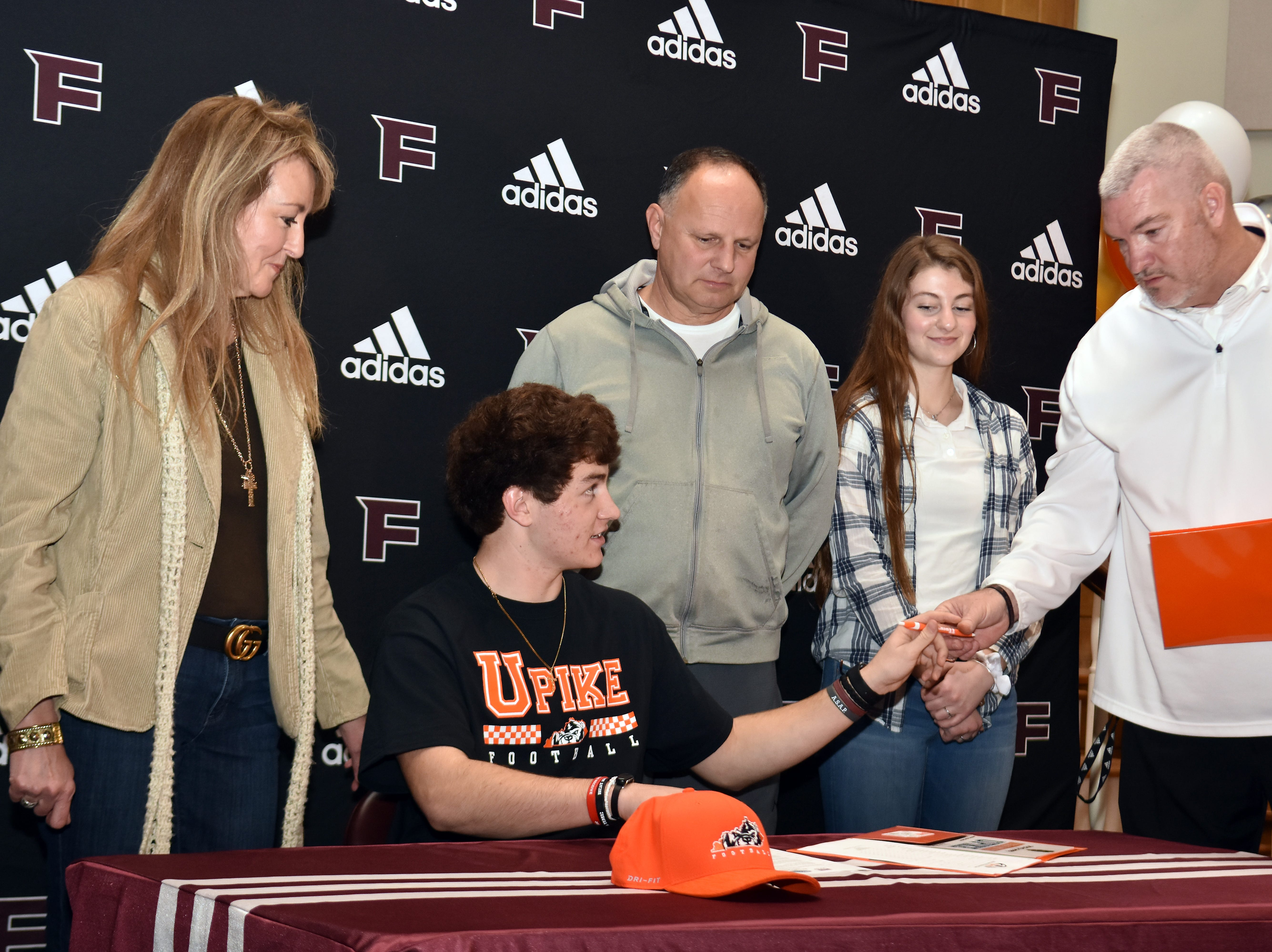 Fulton's Michael Hobby is surrounded by family as he signs to play football at University of Pikeville on National Signing Day, Wednesday, February 6, 2019.