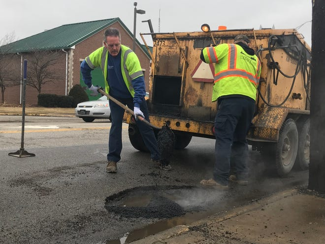 Bryan Wenning and Audie Ric fill a pothole with hot asphalt at the corner of Teal Road and 18th Street. Lafayette Street Department crews have been working overtime after subzero temperatures quickly thawed and created even more potholes.