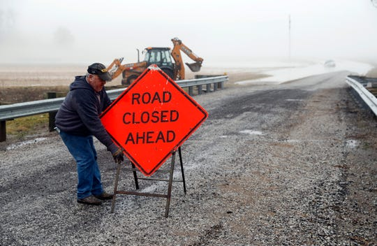 Rushcreek Township Trustee Dave Myers drags a road closed sign into a middle of Holliday Road near Bremen Road Wednesday, Feb. 6, 2019. Myers said an SUV was swept off the road after the driver attempted to go through more than a foot of water.