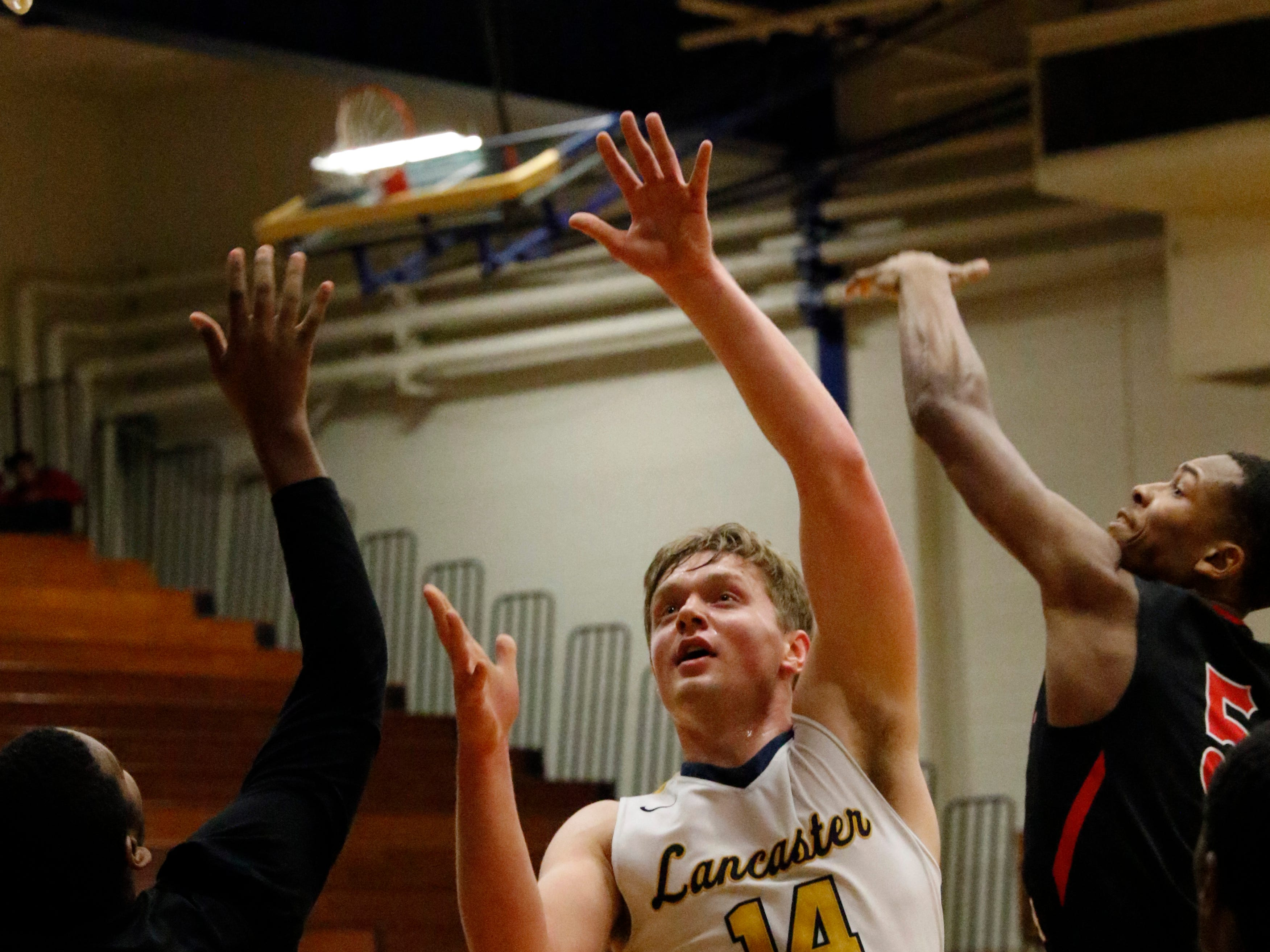 Lancaster's Owen Snyder jumps for a rebound during Tuesday night's game, Feb. 5, 2019, against Groveport Madison at Lancaster High School in Lancaster. The Golden Gales lost the game 47-40.