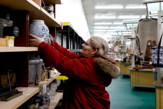Nancy Waldrum, from Logan, places a jar on shelf at her booth Wednesday morning, Feb. 6, 2019, at Peddler's Junction in Lancaster. The vendor market opened on Feb. 1 former location of Lancaster Sales.