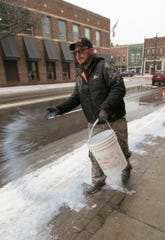 Josh Tefft of Mayhew Tree Farm throws rock salt on the sidewalk of Michigan Ave. in downtown Howell Wednesday, Feb. 6, 2019.
