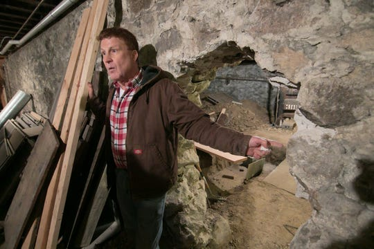 While construction in the basement of the future 1883 Bistro & More is still in the rough stages, bistro co-owner Don Waldenmayer points out the 2-foot thickness of the stone walls that separate what will be two areas of a wine cellar in a tour of the downtown Fowlerville buildings, Wednesday, Feb. 6, 2019.