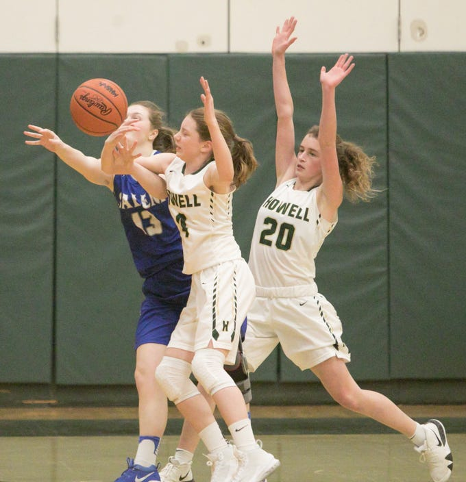 Howell's Lillia McCurdy knocks the ball away from Salem's Jaclyn Deprez, with fellow Highlander Evelyn Pennala on guard in the game at Howell Tuesday, Feb. 5, 2019.