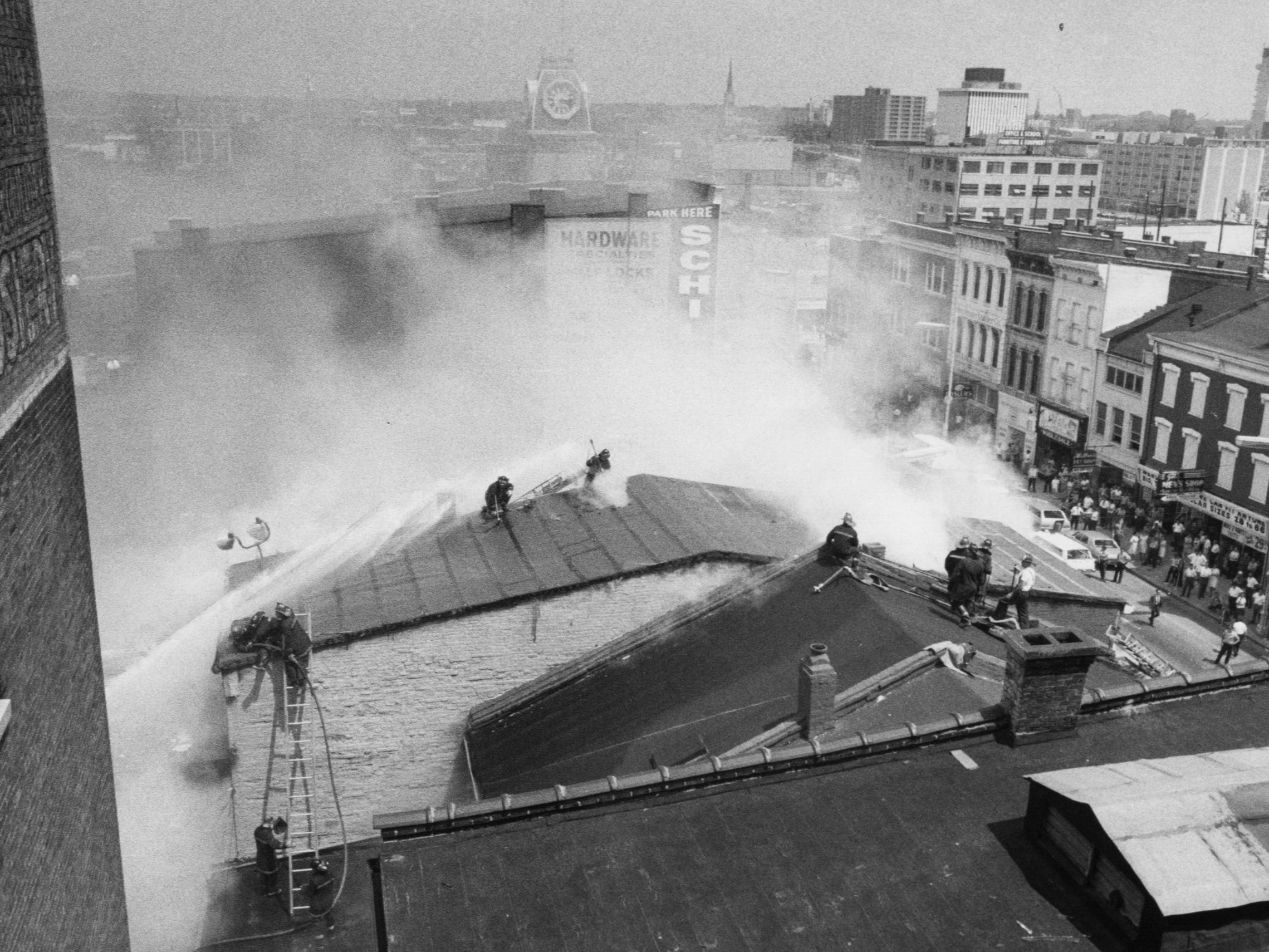 Firemen, shrouded in smoke, battle Bridges-Smith Paint Co. fire from the roof. 