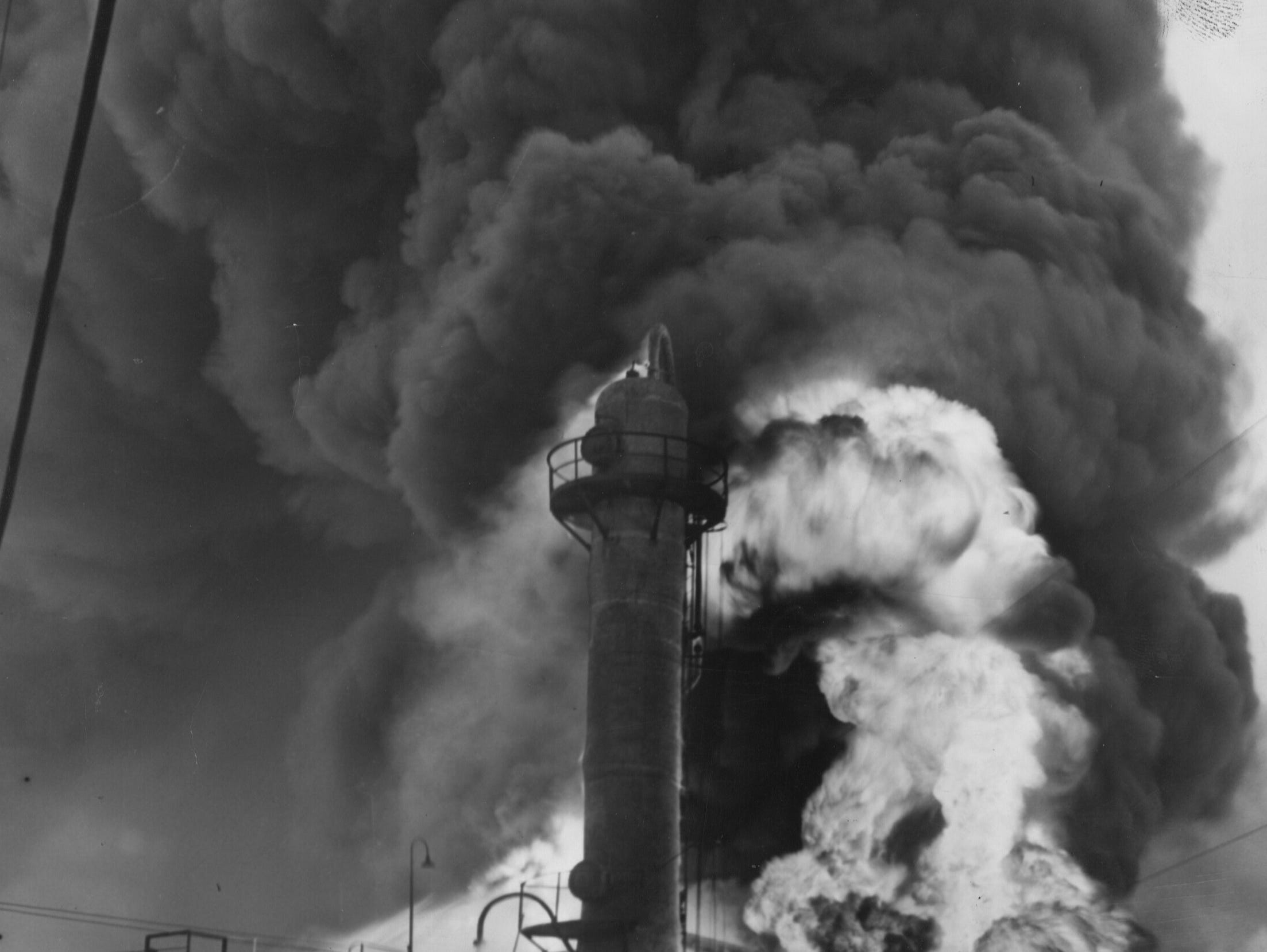"Clouds of smoke poured skyward as firemen fought a fire at the ""crackling"" plant of the Stoll Oil Refining Company. 