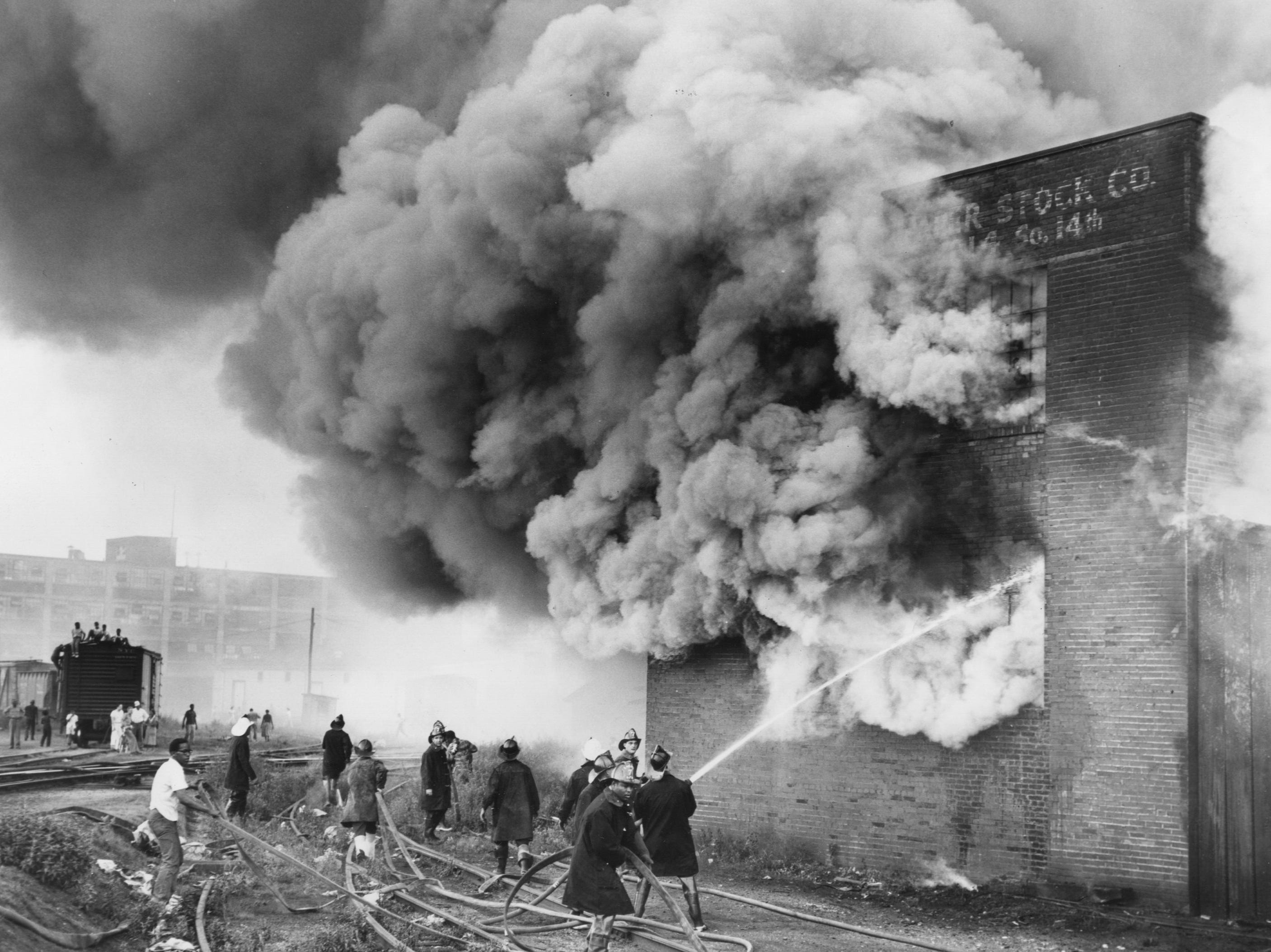 Firemen battle flames that destroyed the interior of the Sanders Paper Stock Company. 