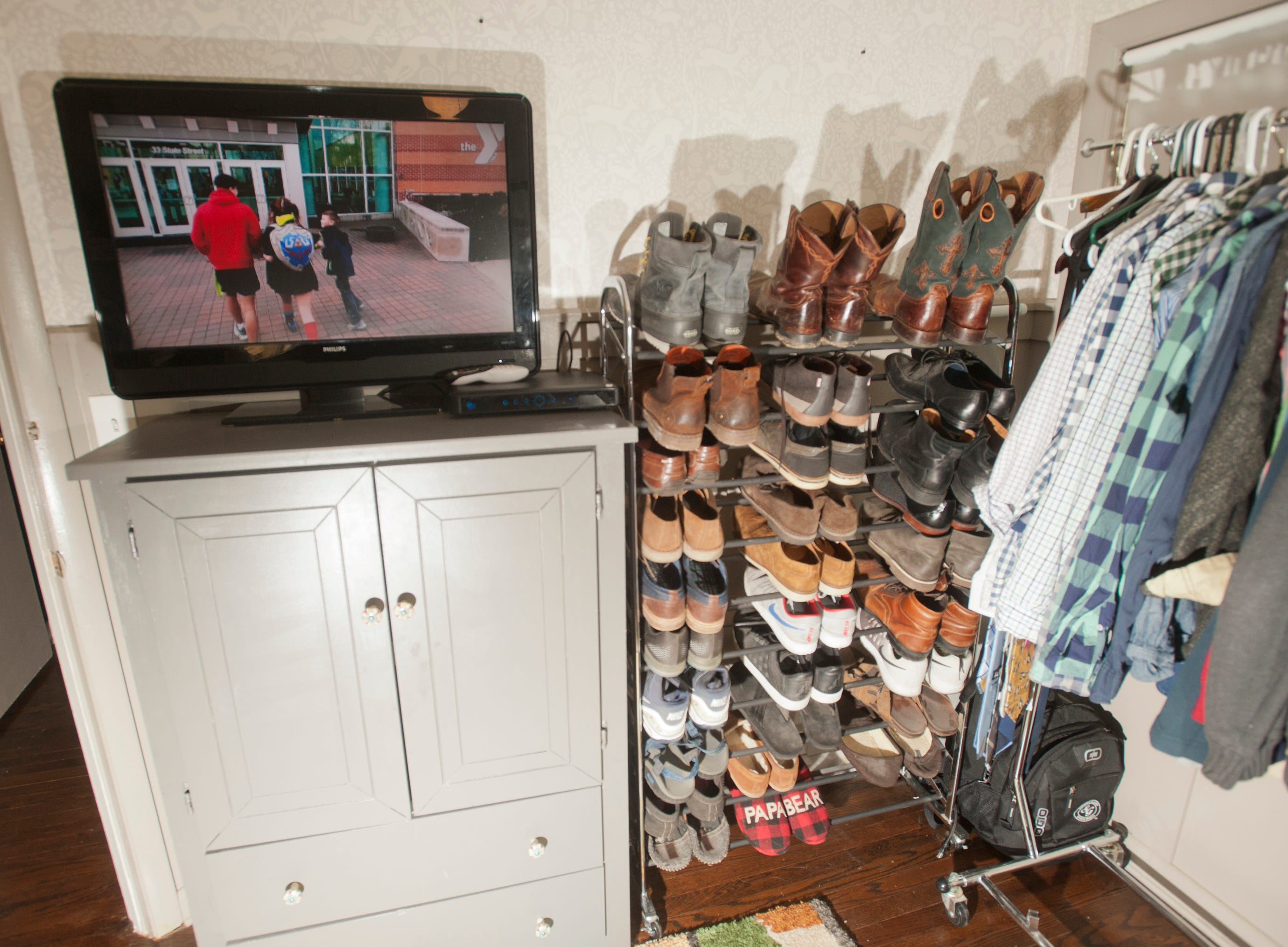 A television sits atop a cabinet next to racks of shoes and clothing.