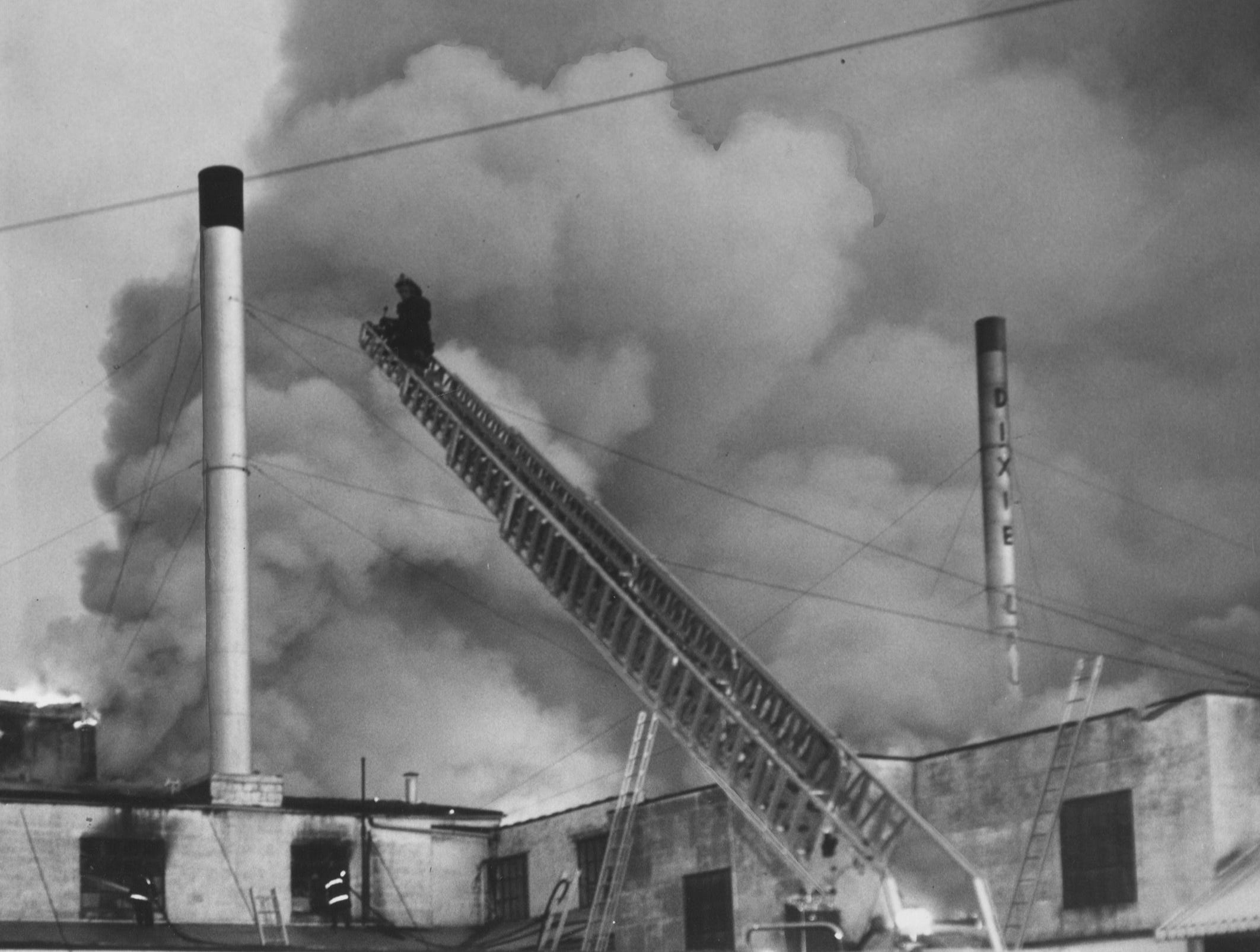 An aerial-ladder truck moves into position to fight the early-morning fire that swept the Dixie Launudry. 