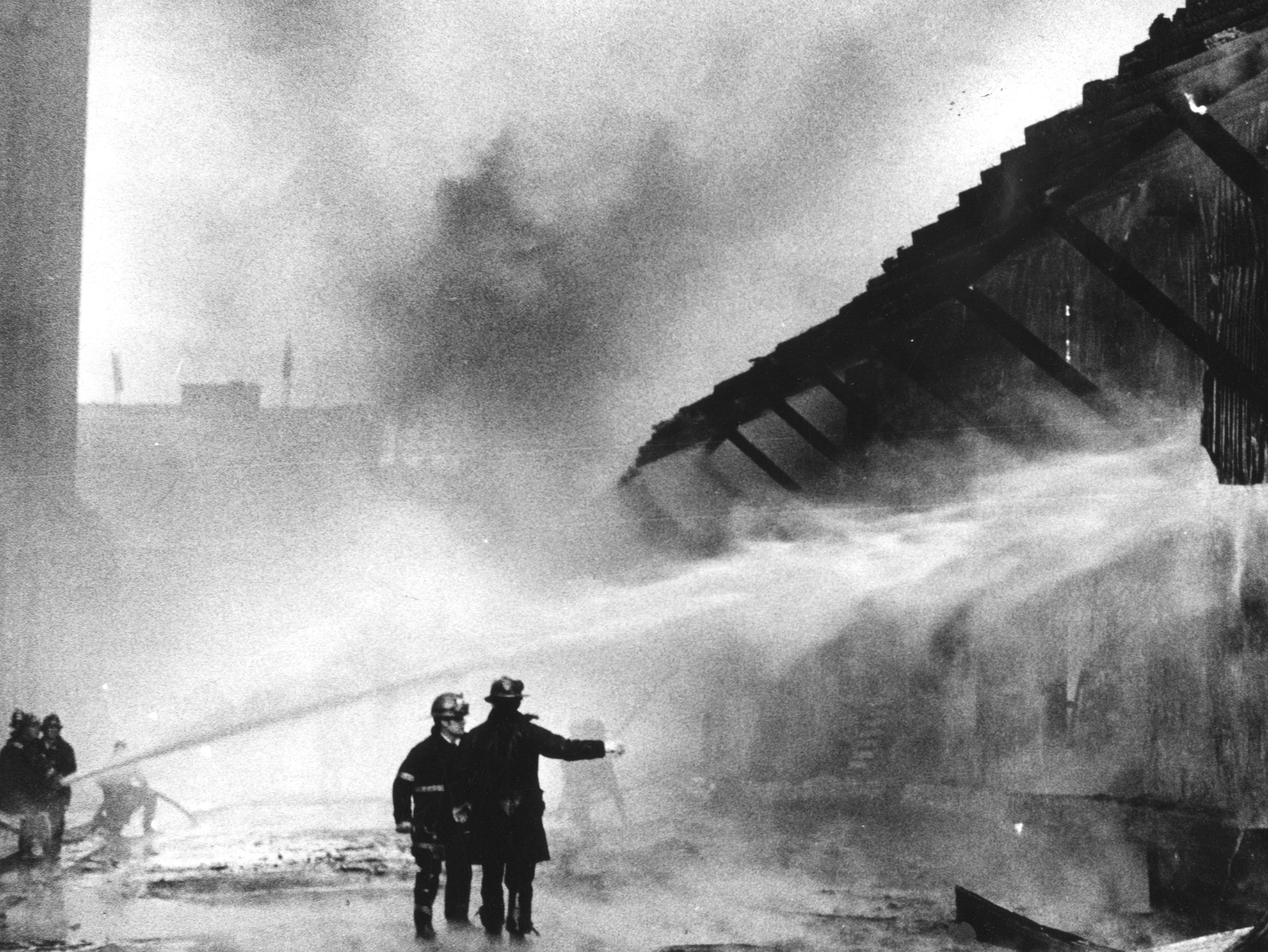 Fire fighters try to keep a two-alarm fire spreading from the building housing Allen Robertson & Co., a farm-supply firm. 