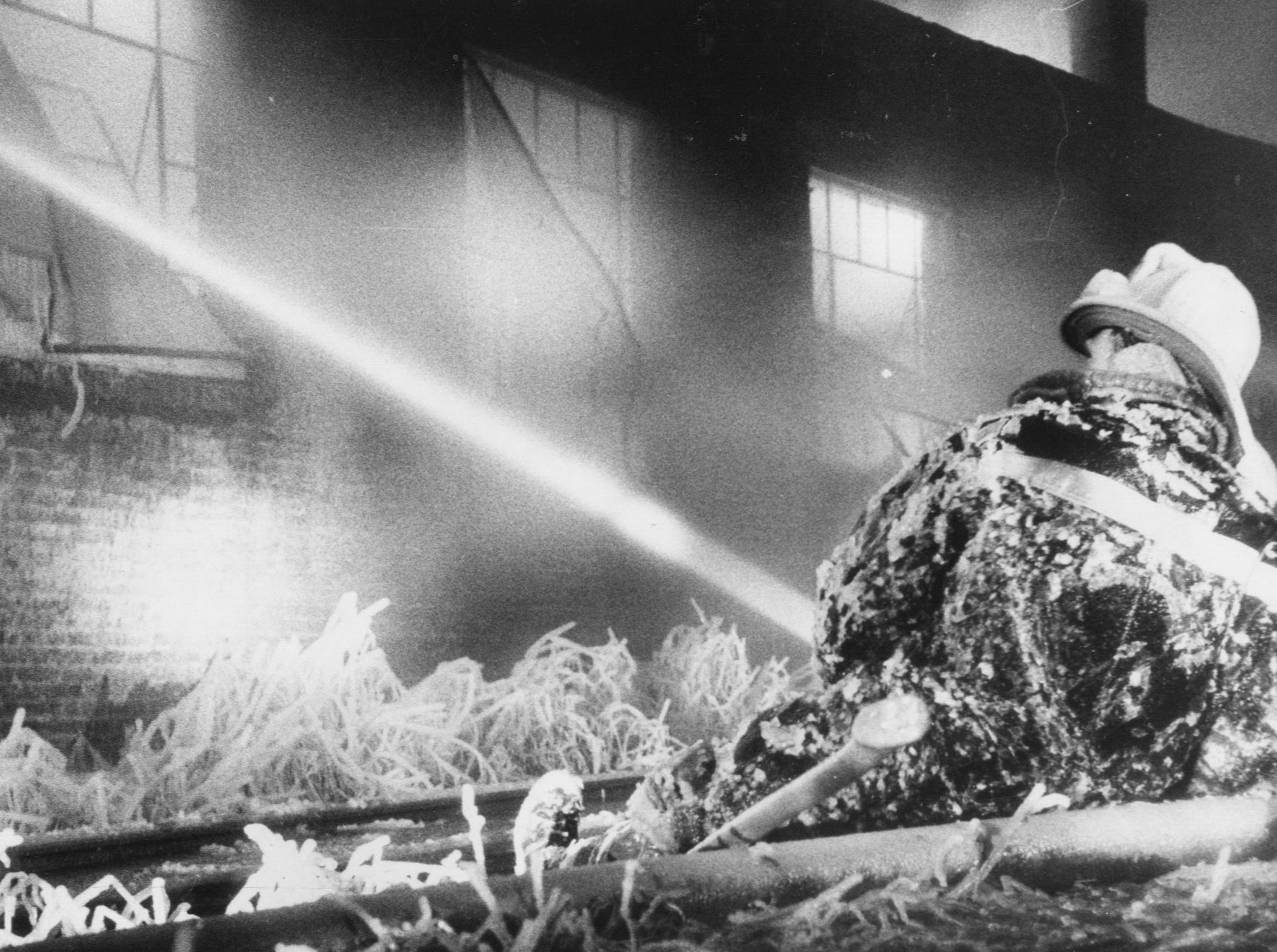 An ice-coated Louisville fireman, William Riedinger of Engine 3, braces himself against railroad ties during a three-alarm fire which destroyed the main building at Conner Manufacturing Co. last night. 
