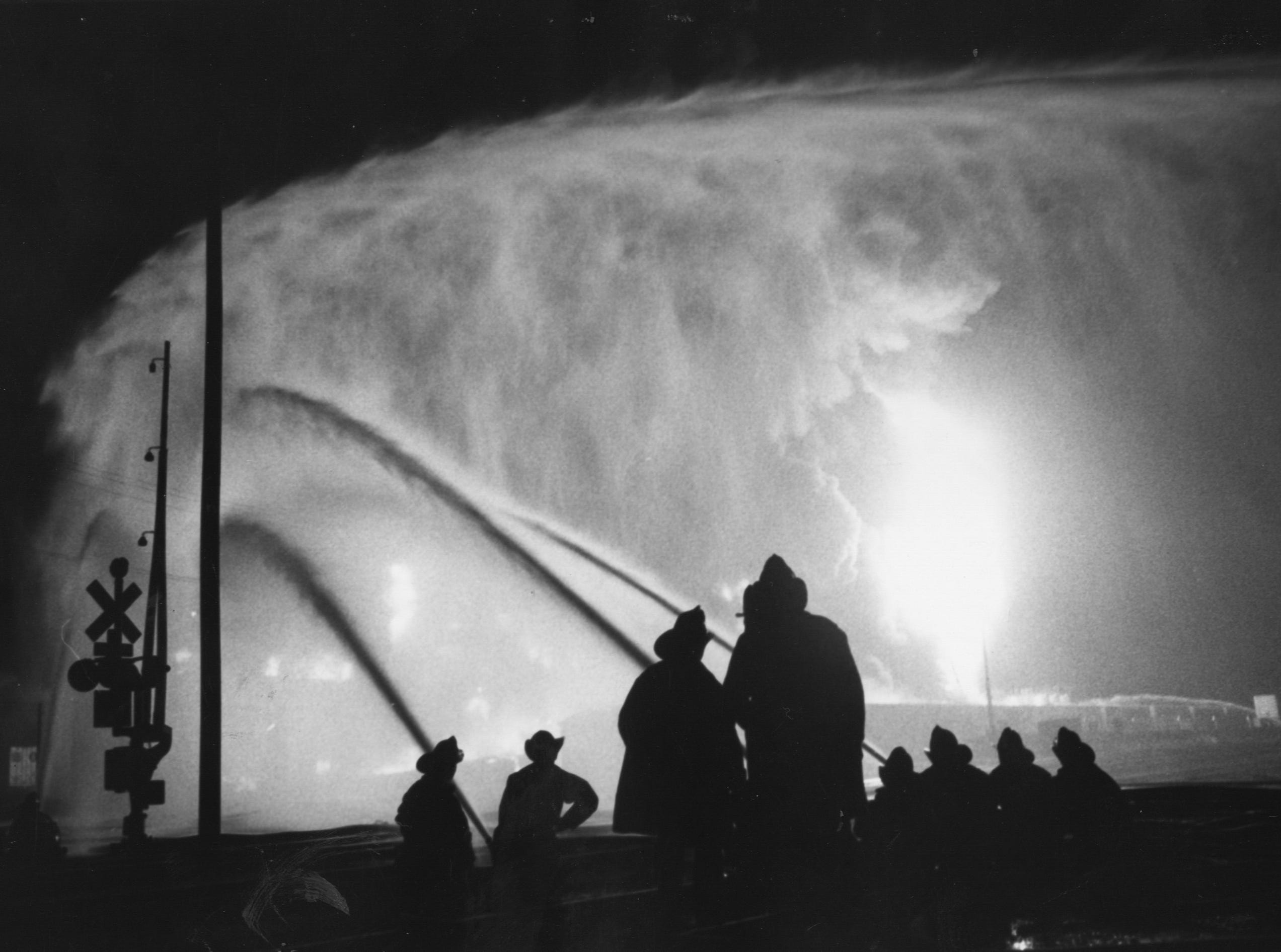 Fingers of water try to cool the intense heat as flames lick around the Bronco Co. storage facilities at 14th and Kentucky. 