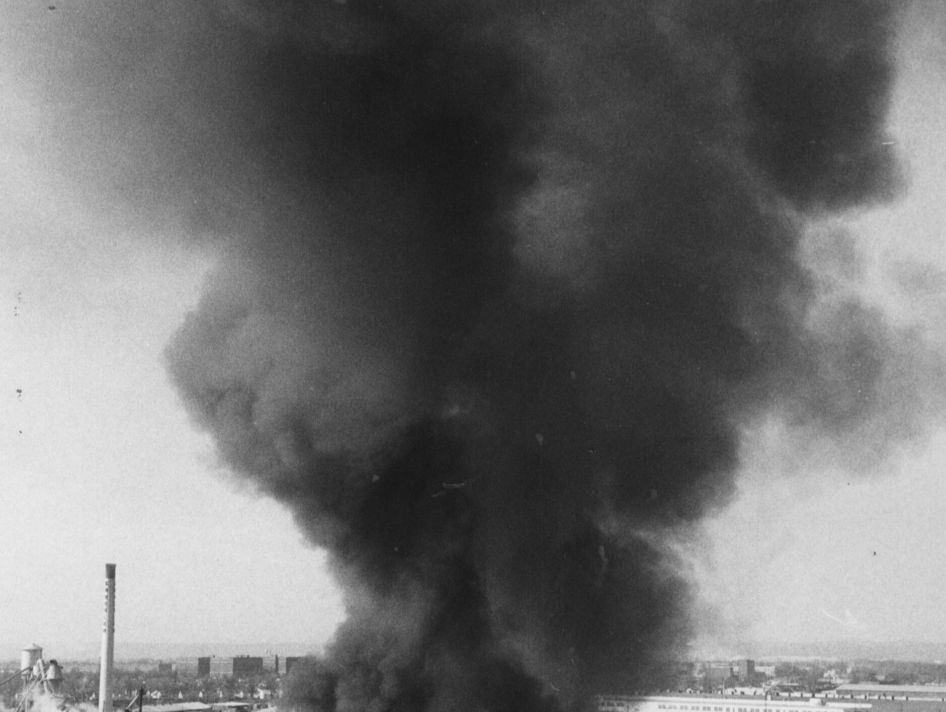 A plume of black smoke rises from a three-alarm fire that heavily damaged the Allied Drum Service Co. just west of the University of Louisville yesterday. 