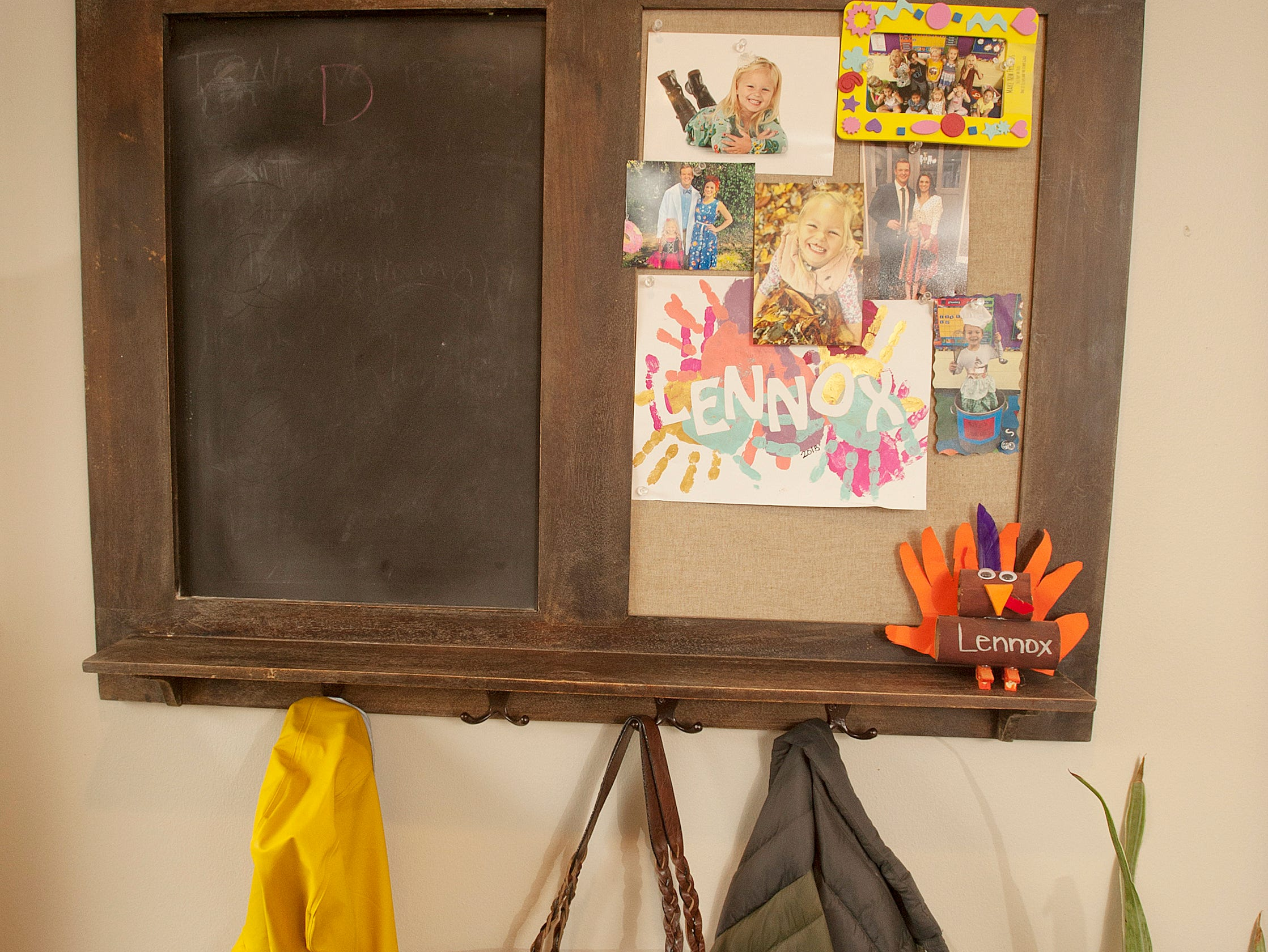 Just inside the living room door is this combined blackboard, coat rack and tack board decorated with photos of Squires' daughter, Lennox, age 5.