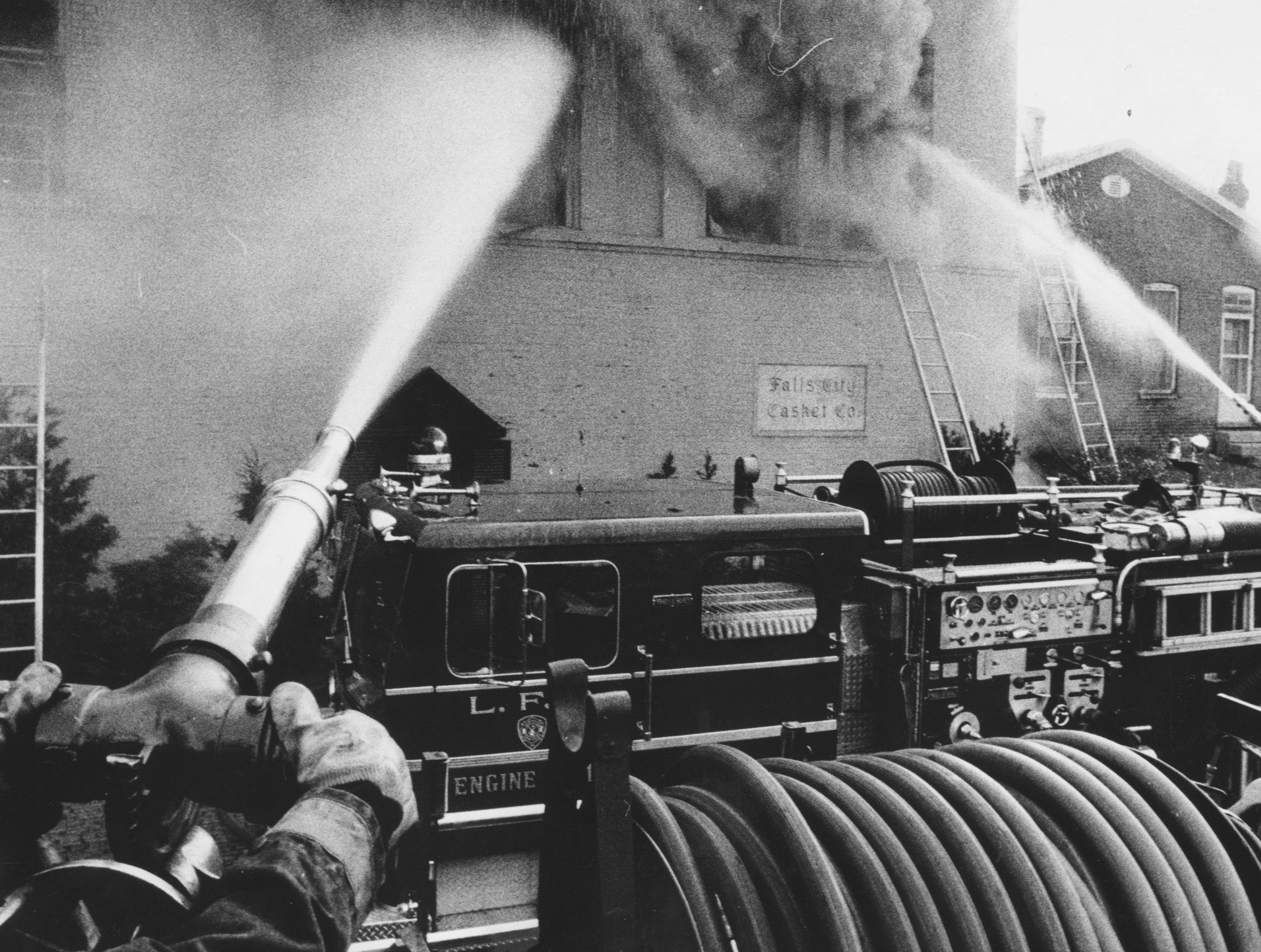 Firemen trained high-pressure nozzles on the second floor of the Falls City Casket Co at 1734 Garland while fighting a three-alarm blaze that extensively damaged the building yesterday. 