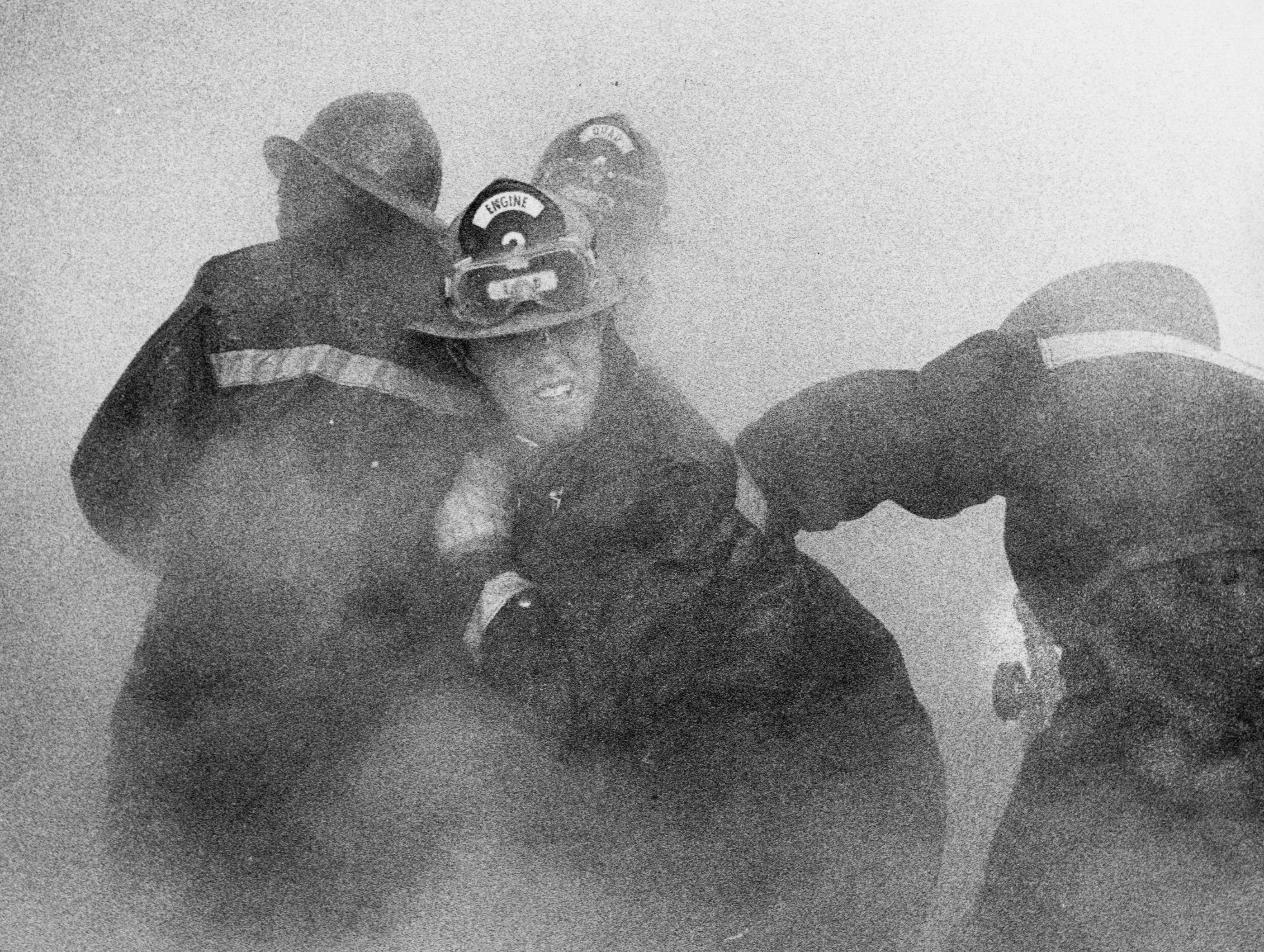 Firemen from Engine 2 and Squad 4 grimace from smoke while fighting a warehouse fire at 721 S. 26th St. 