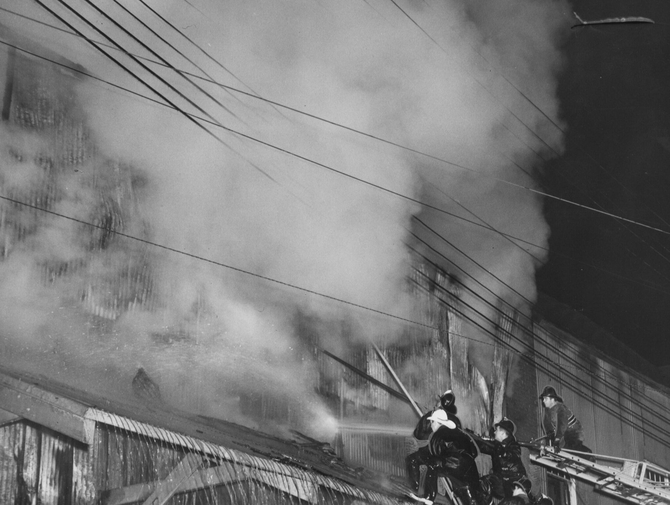 Firemen street level fight the blaze through a broken door panel as other direct hose streams from extension ladders and a hydraulic-lift tower during the fire that destroyed the Superior Paper warehouse building. 