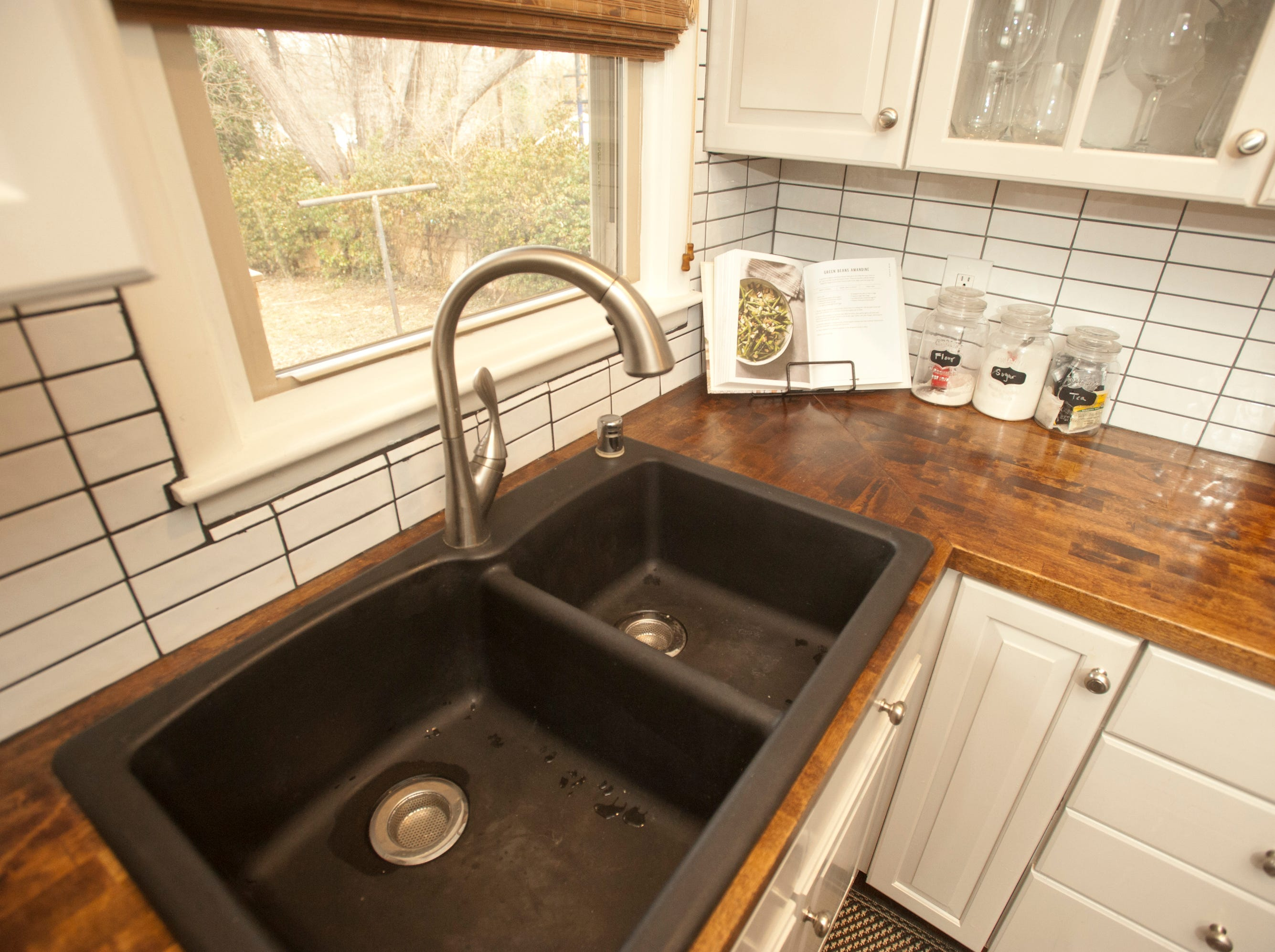 The kitchen counter top is made of sealed butcher block stained to match the color of the wood floors. The backsplash is a grid patterned ceramic subway tile.