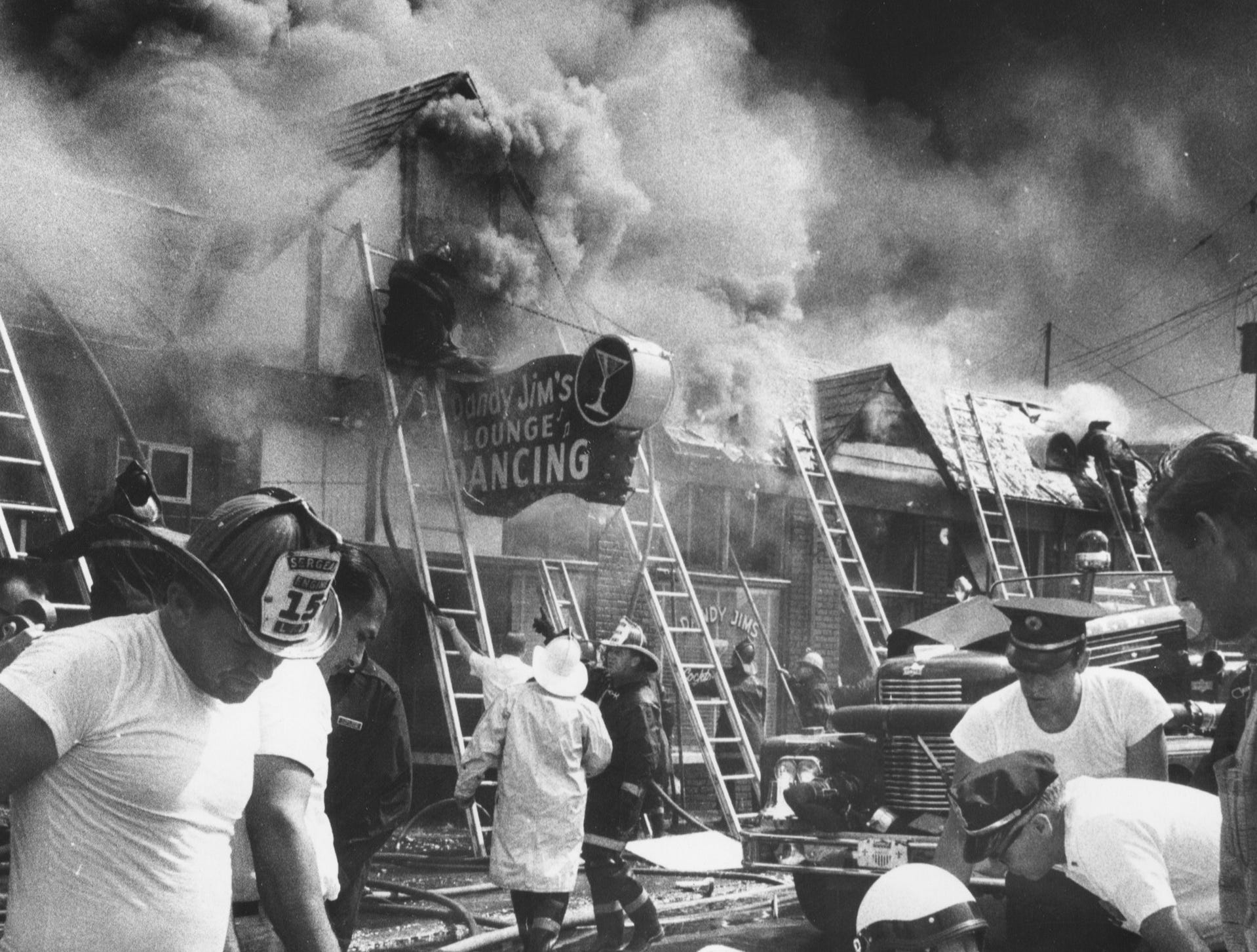 A fallen fireman receives oxygen as smoke and flames gush from a 4,000-square-foot commercial building housing Jim Dandy's Restaurant at Oak and Preston in Louisville yesterday. 