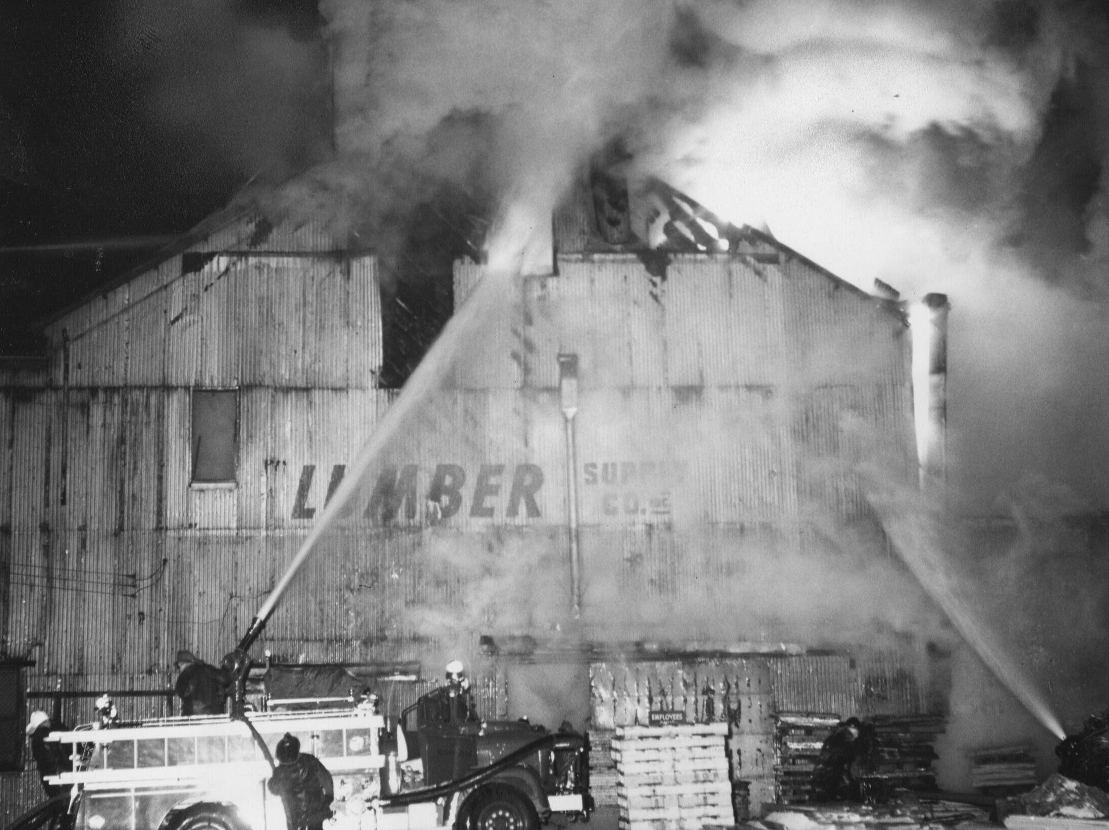 Hot duty on a cold night a firemen work in 20-degree temperatures and on ice-covered streets, battled a fire at the Lumber Supply Company.