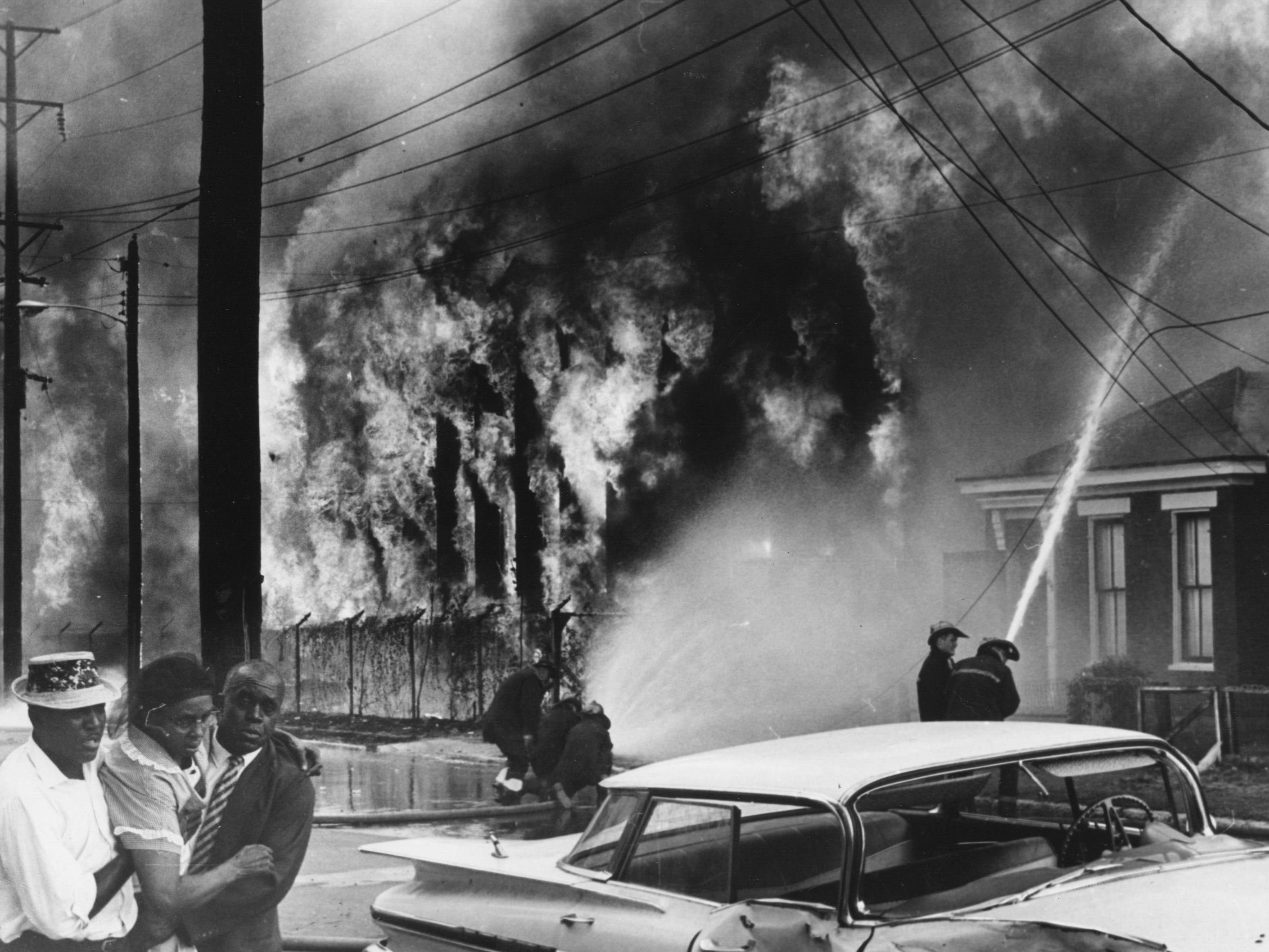 A four-alarm fire at the old Woolen Mills also damaged 12 nearby houses. 