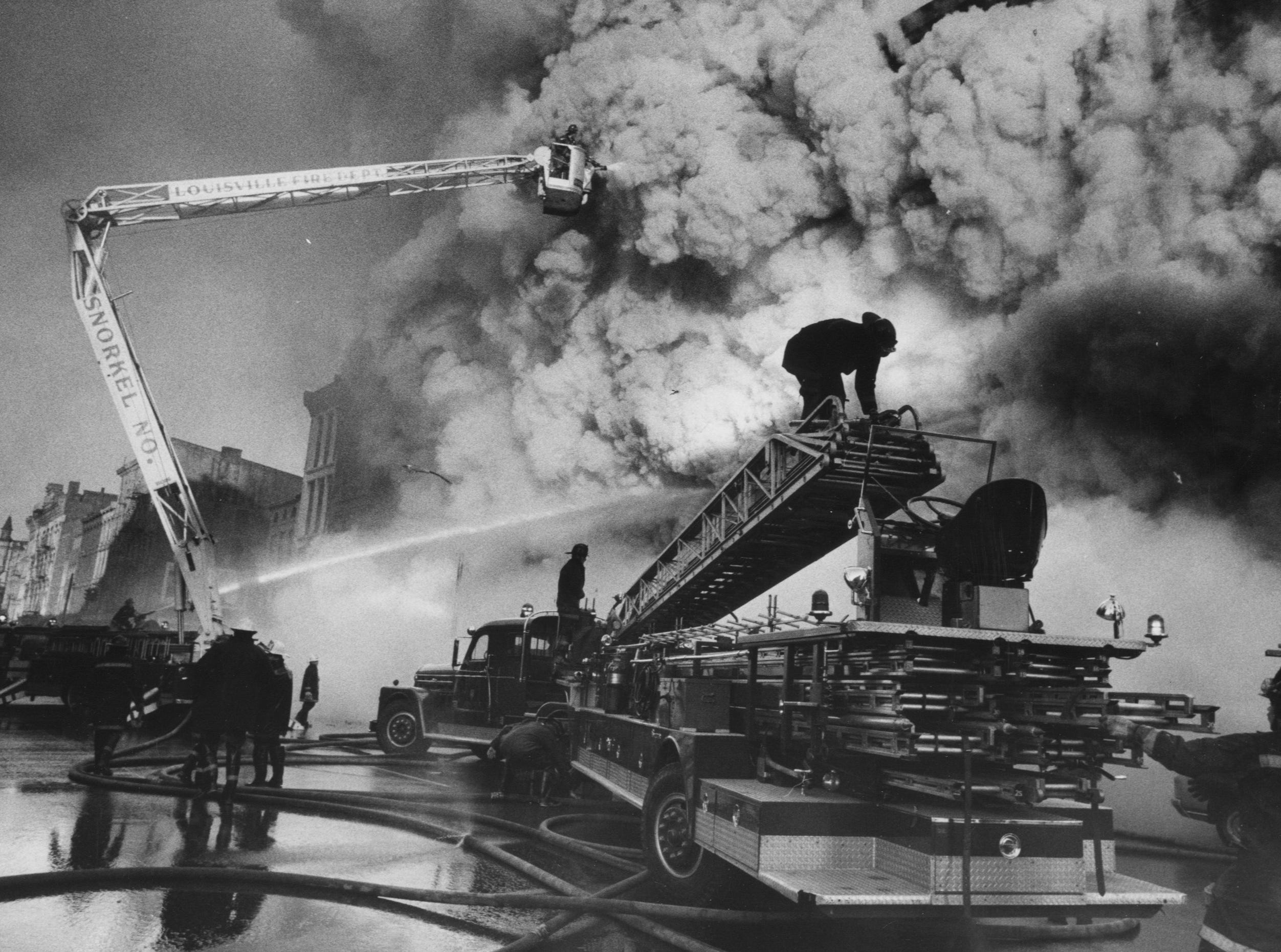Firemen battle a three-alarm fire as smoke pours fro the building that housed the Harry R Hibbs hat and glove company. 