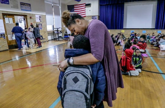Semple Elementary principal Danielle Randle hugs an arriving student during the school's morning meeting. 