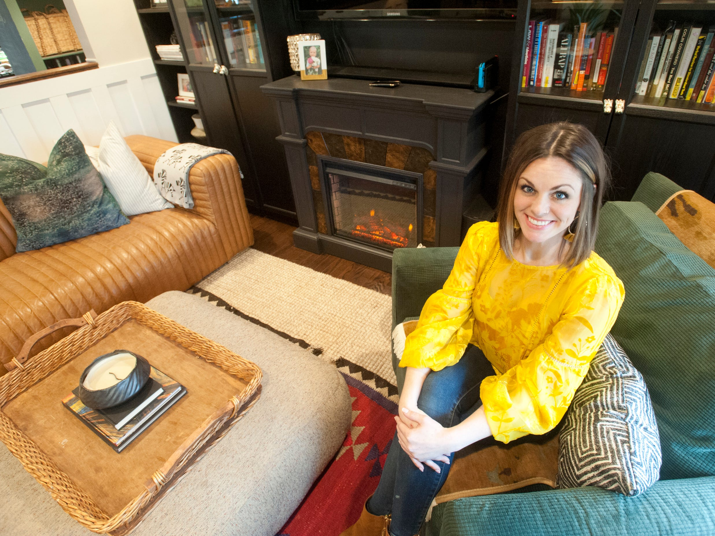 Professional home decorator Skye Squires' relaxes in her Hikes Point living room. Squires, an avid reader, created a black wall of built-in bookcases, electric fireplace and large screen television (which is black when it is off.)