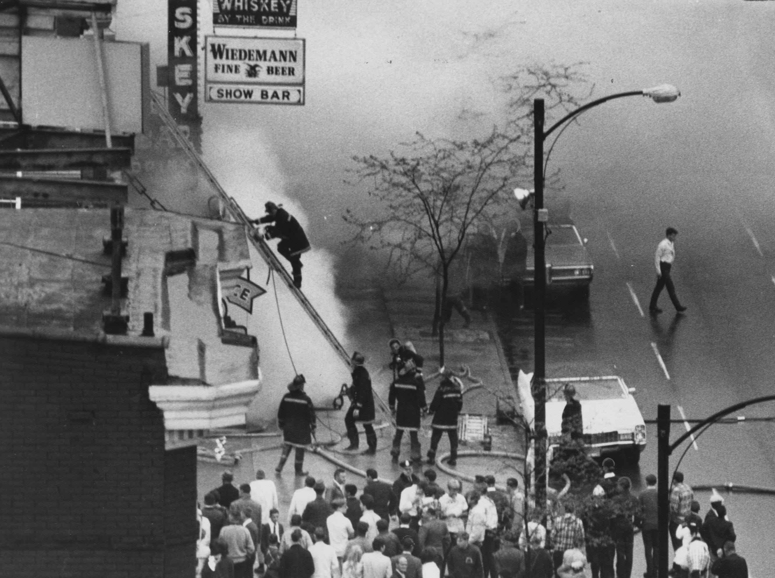 A fireman climbs a ladder to get in better position to fight fire that gutted three-business fun center in the 400 block of W. Broadway. 