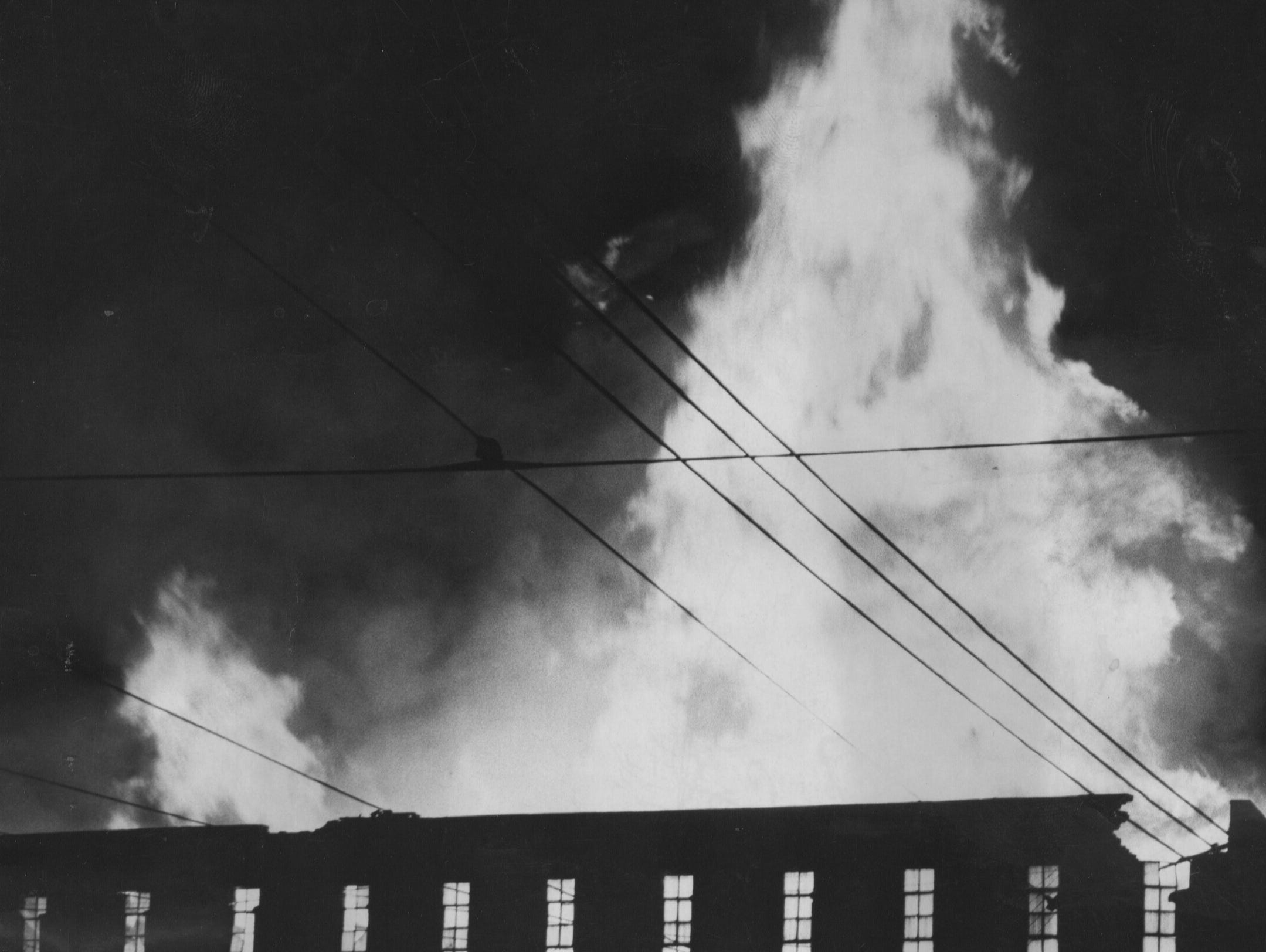 Flames shot 100 feet in the air last night from the burning five-story warehouse at the Karl Nussbaum iron wires and supply yard. 
