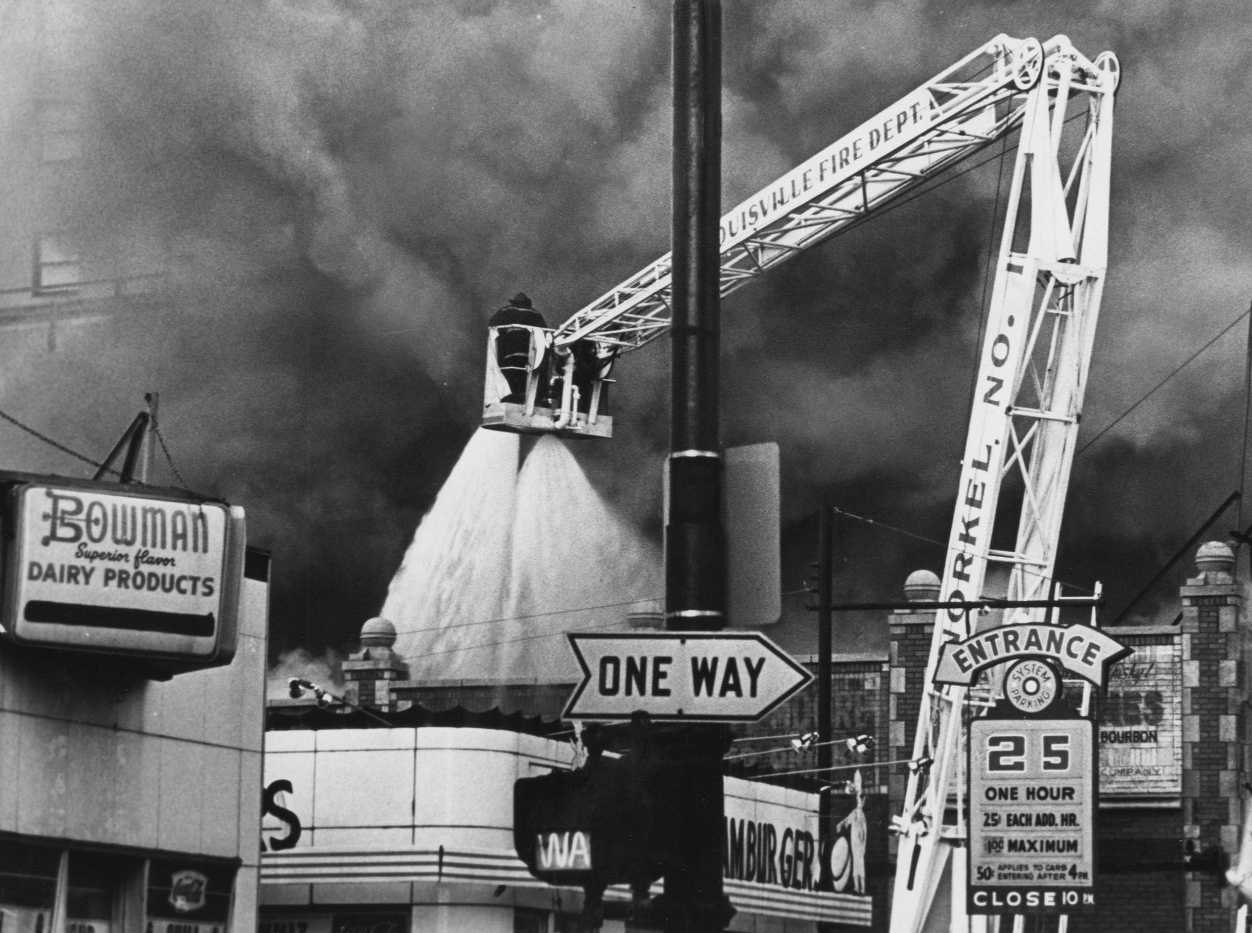 A snorkel truck reached its long arm above Dinty Moore's show bar to dump thousands of gallons of water on the roof of the building which also housed Playhouse Theater and a game center. 