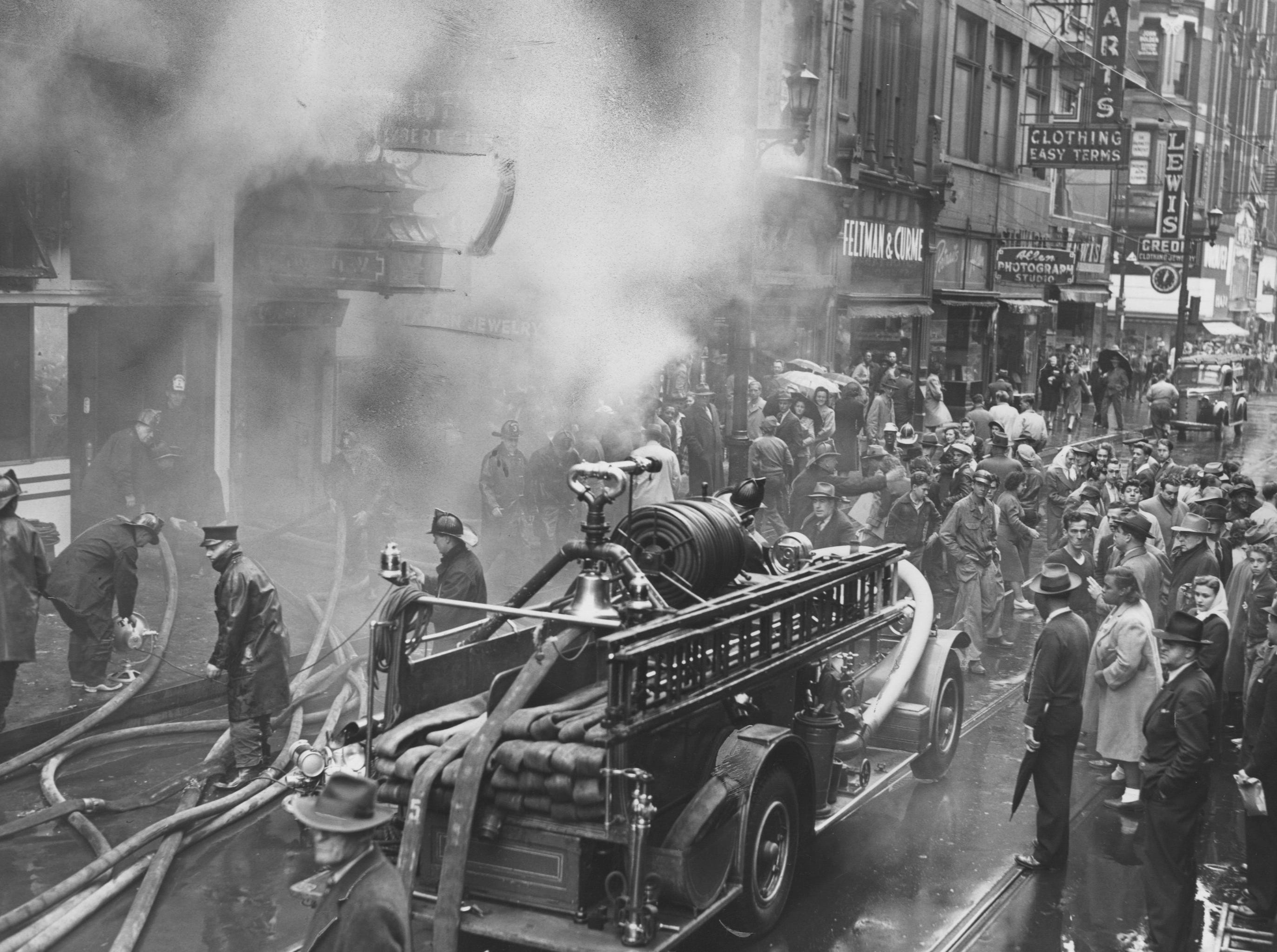 Smoke is pouring from the Roy E. Steele Shoe Shop. Fire gutted the shop basement and first floor. 
