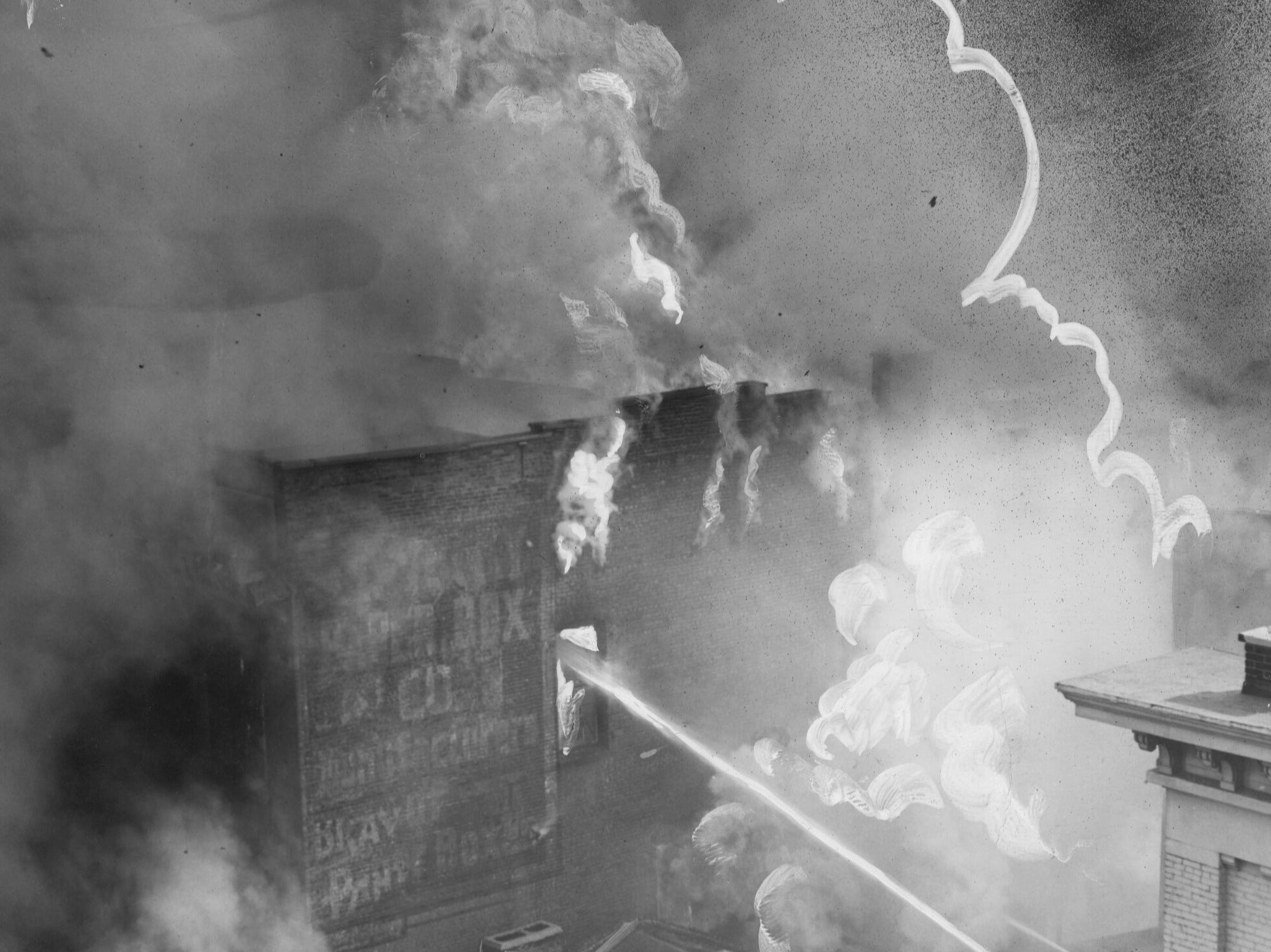 A tower of flames roar up from the Kentucky Paper Box Co. and the Finger Box Co. as firemen on near-by roof pour water into windows. 