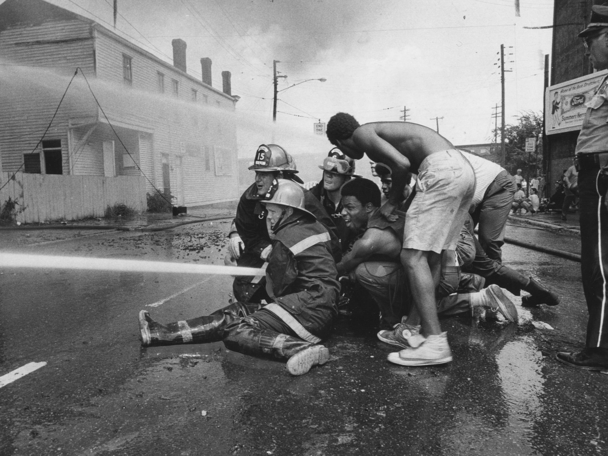Neighbors at the scene gave fire fighters help in handling the high-pressure hoses used to combat the four-alarm blaze. 