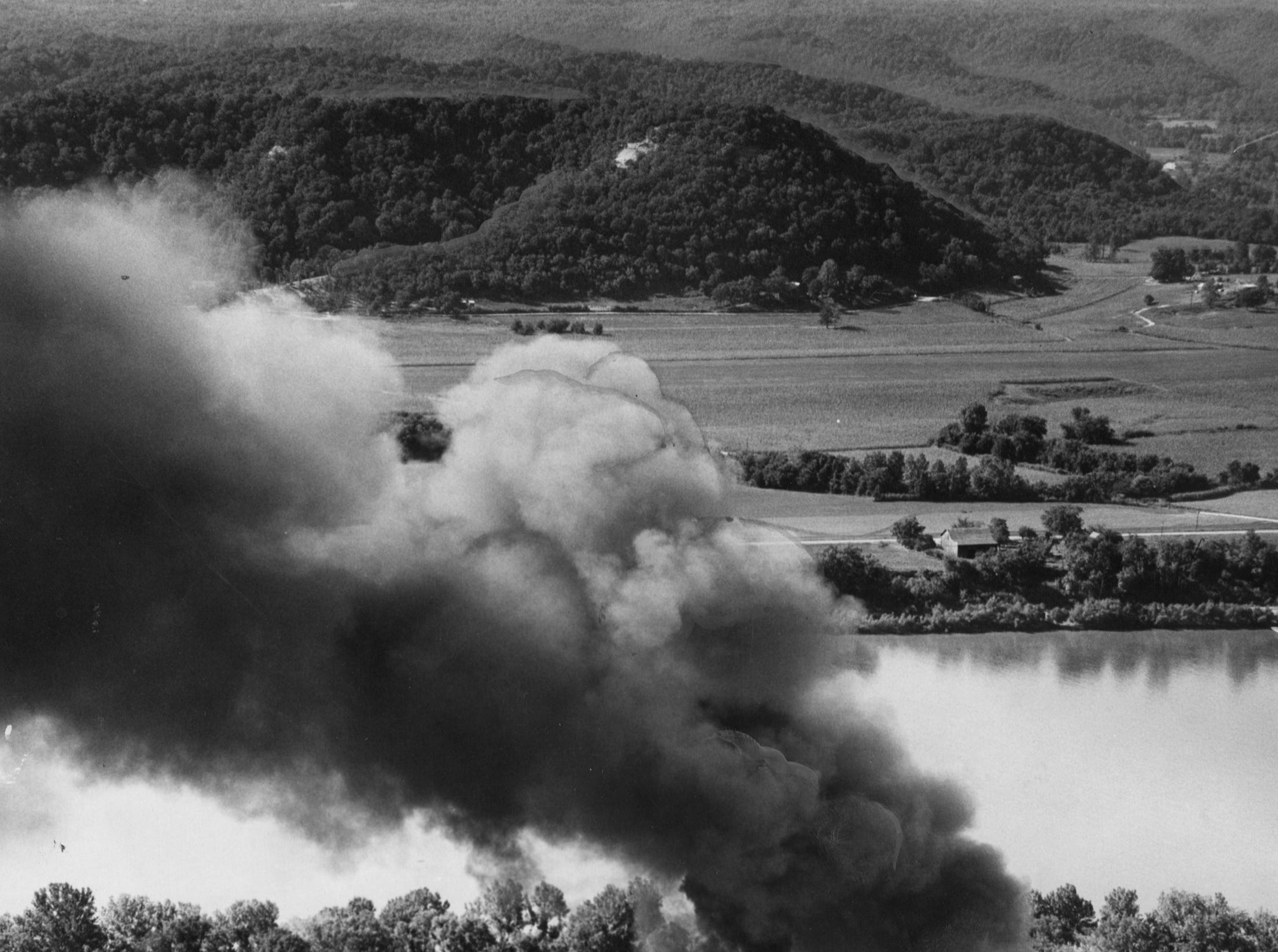 Black smoke billows upward from burning automobile tires, seats and batteries at Harold's Auto Parts on the Ohio River bank at Lee's Lane.