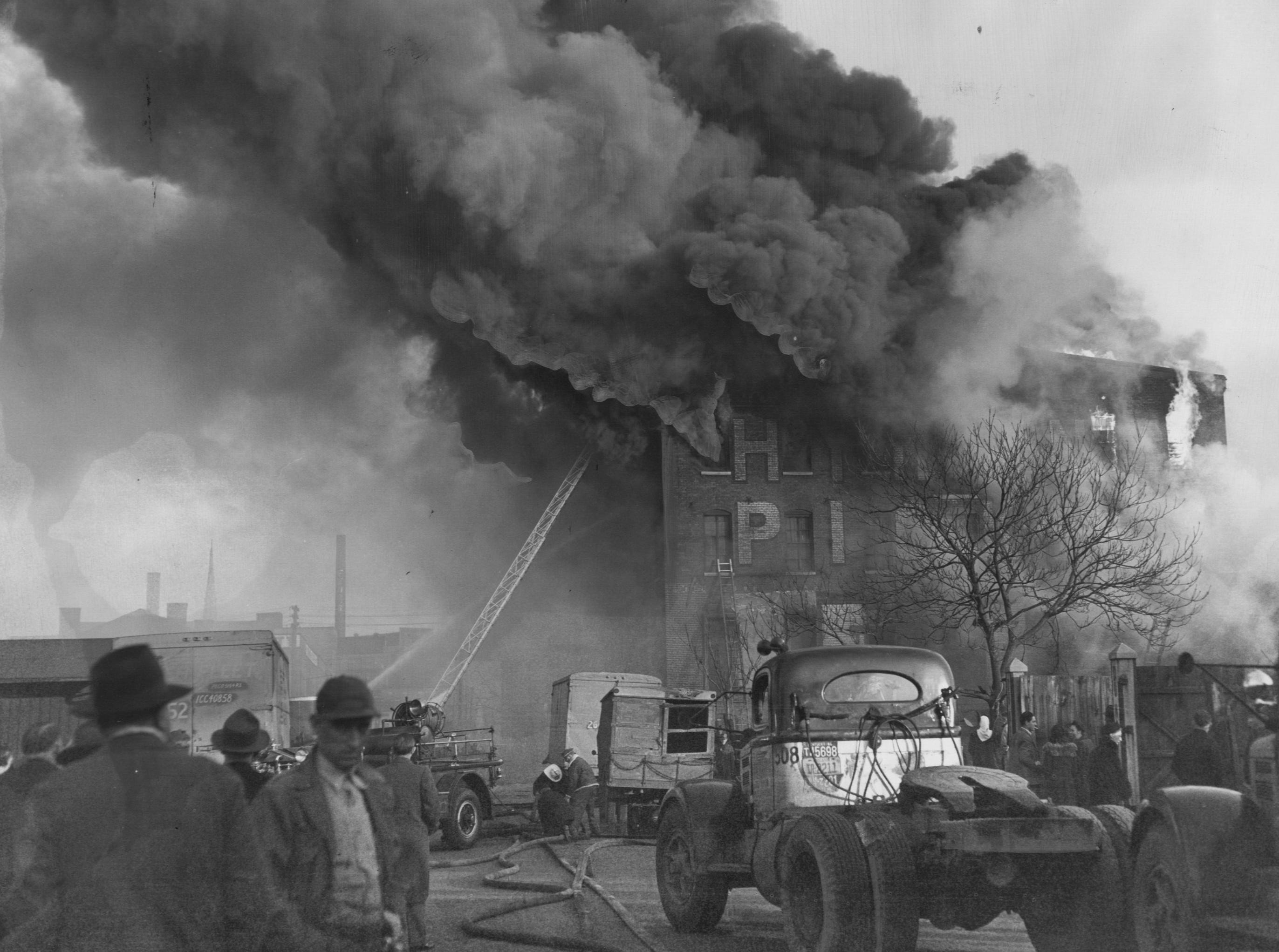 Whipped by a strong wind, flames spurt from windows of the old Hyman Pickle Company building on Pearl between Floyd and Brook. 
