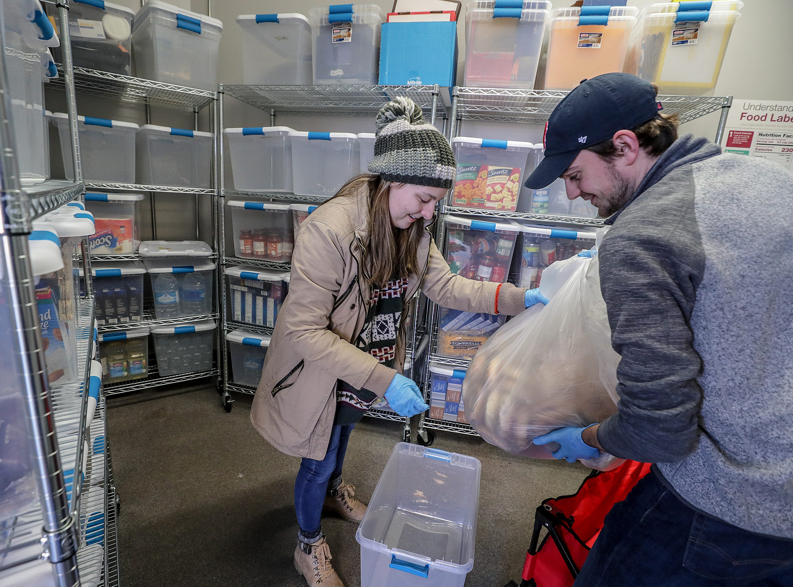 Henny Ransdell, left, and Ryan Buckman, right, take a bag of bagels donated by Einstein Bros. bagels, and put them into a plastic bin at U of L's food bank. Jan. 28, 2019